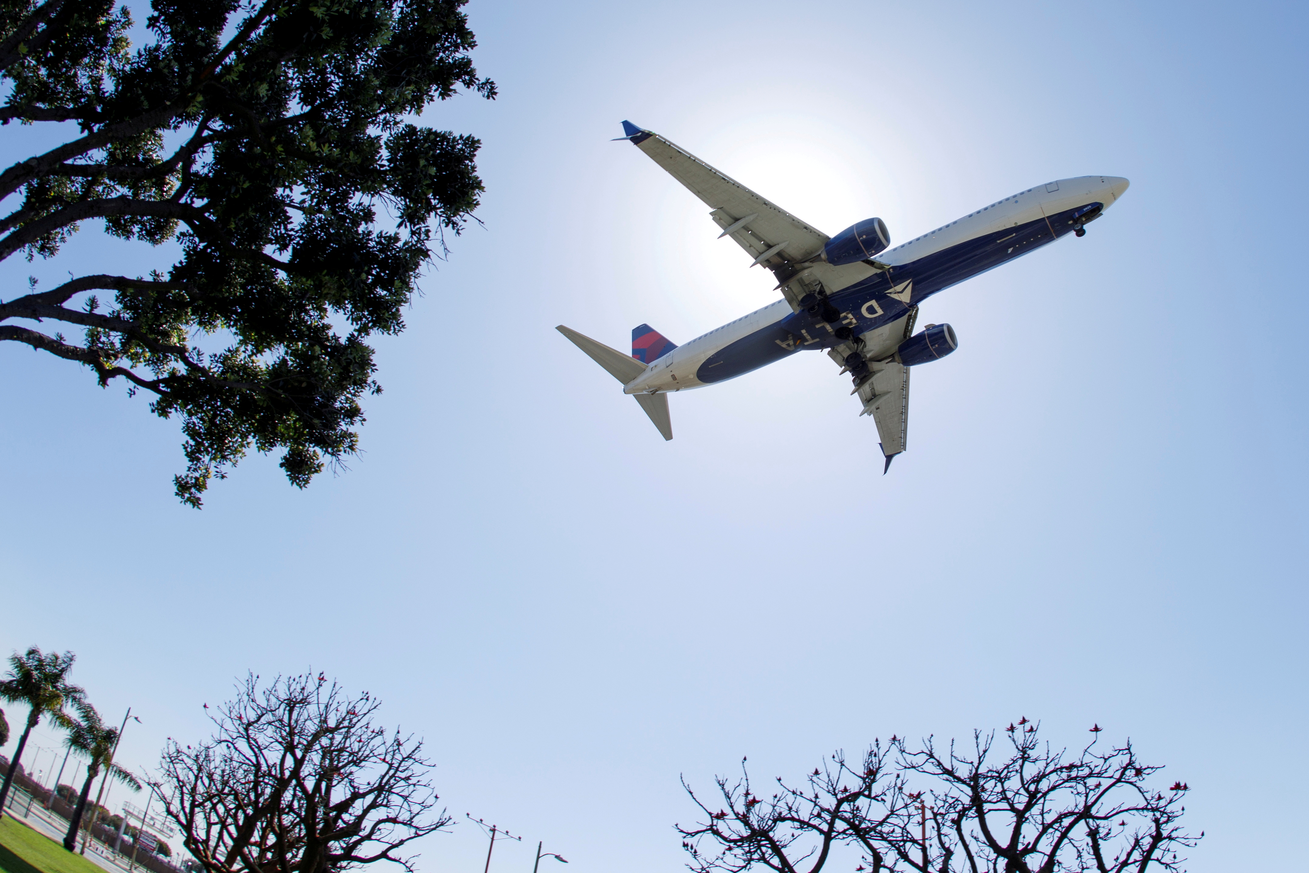 A Delta Airlines passenger jet approaches to land at LAX in Los Angeles, California, U.S., April 7, 2021. REUTERS/Mike Blake/File Photo