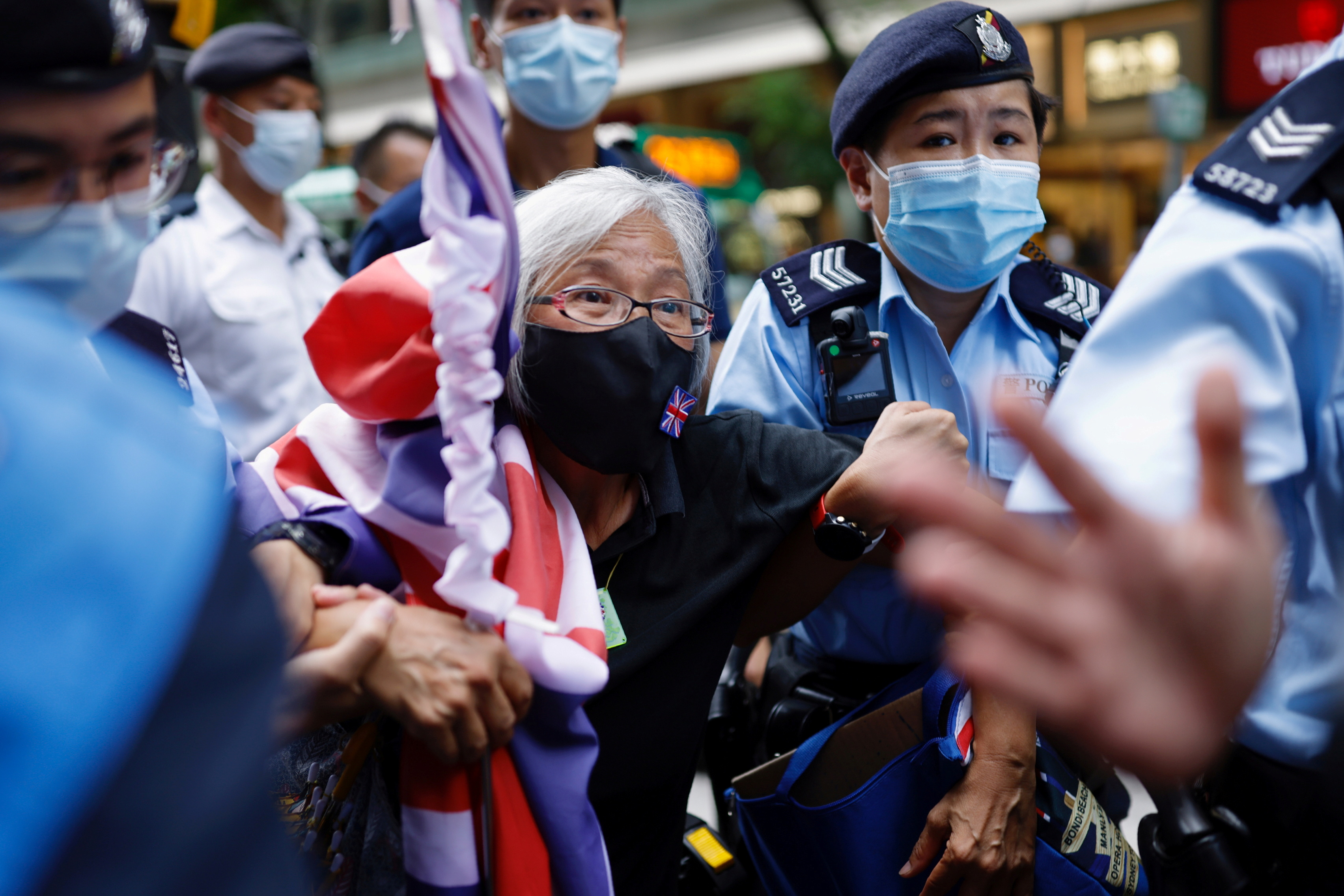 A pro-democracy protester with a Union flag mask is taken by police at Causeway Bay after police denied permission for a protest rally during the 24th anniversary of the former British colony's return to Chinese rule, on the 100th founding anniversary of the Communist Party of China, in Hong Kong, China July 1, 2021. REUTERS/Tyrone Siu