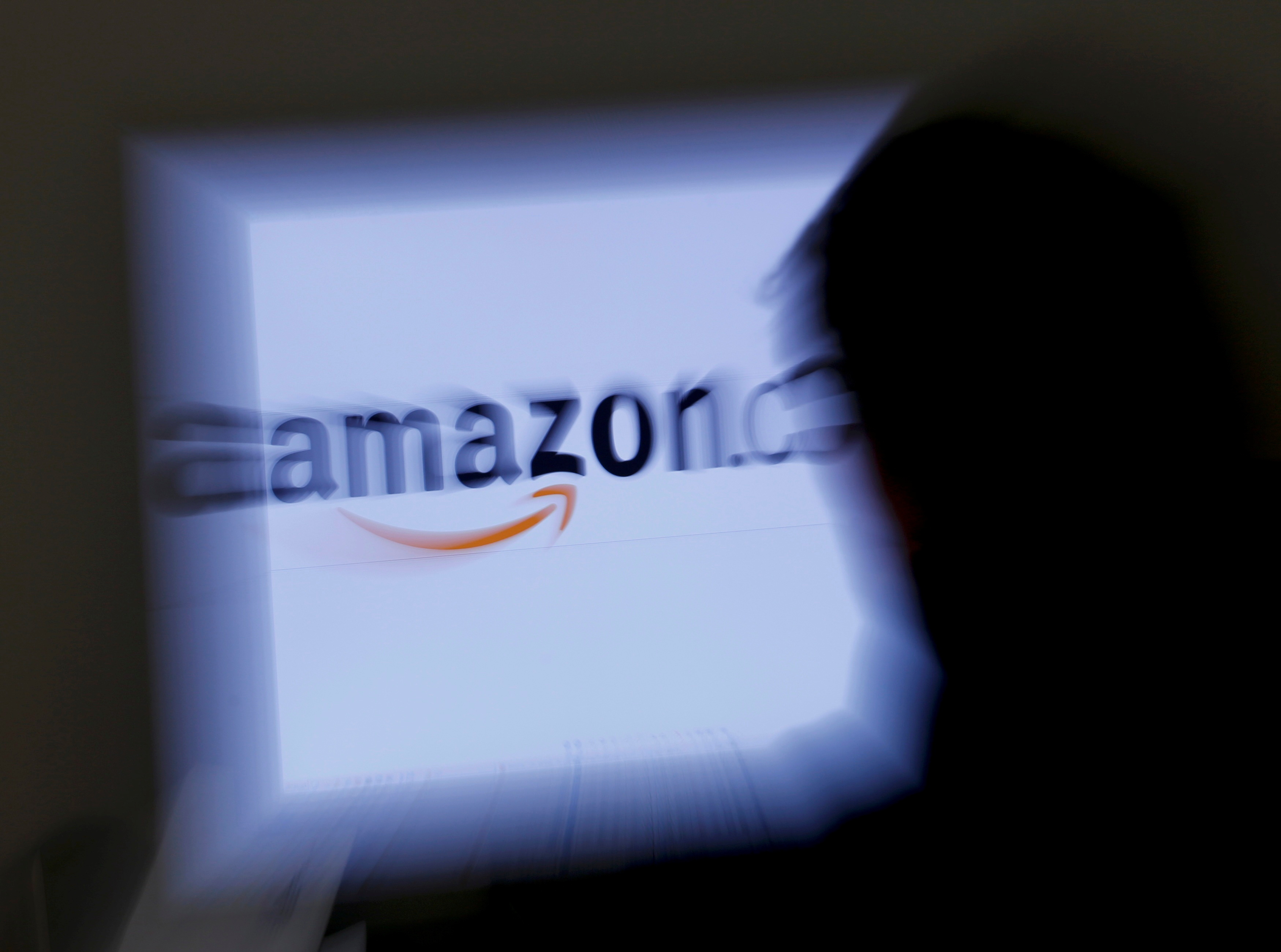 A zoomed illustration image of a man looking at a computer monitor showing the logo of Amazon is seen in Vienna November 26, 2012. REUTERS/Leonhard Foeger/File Photo