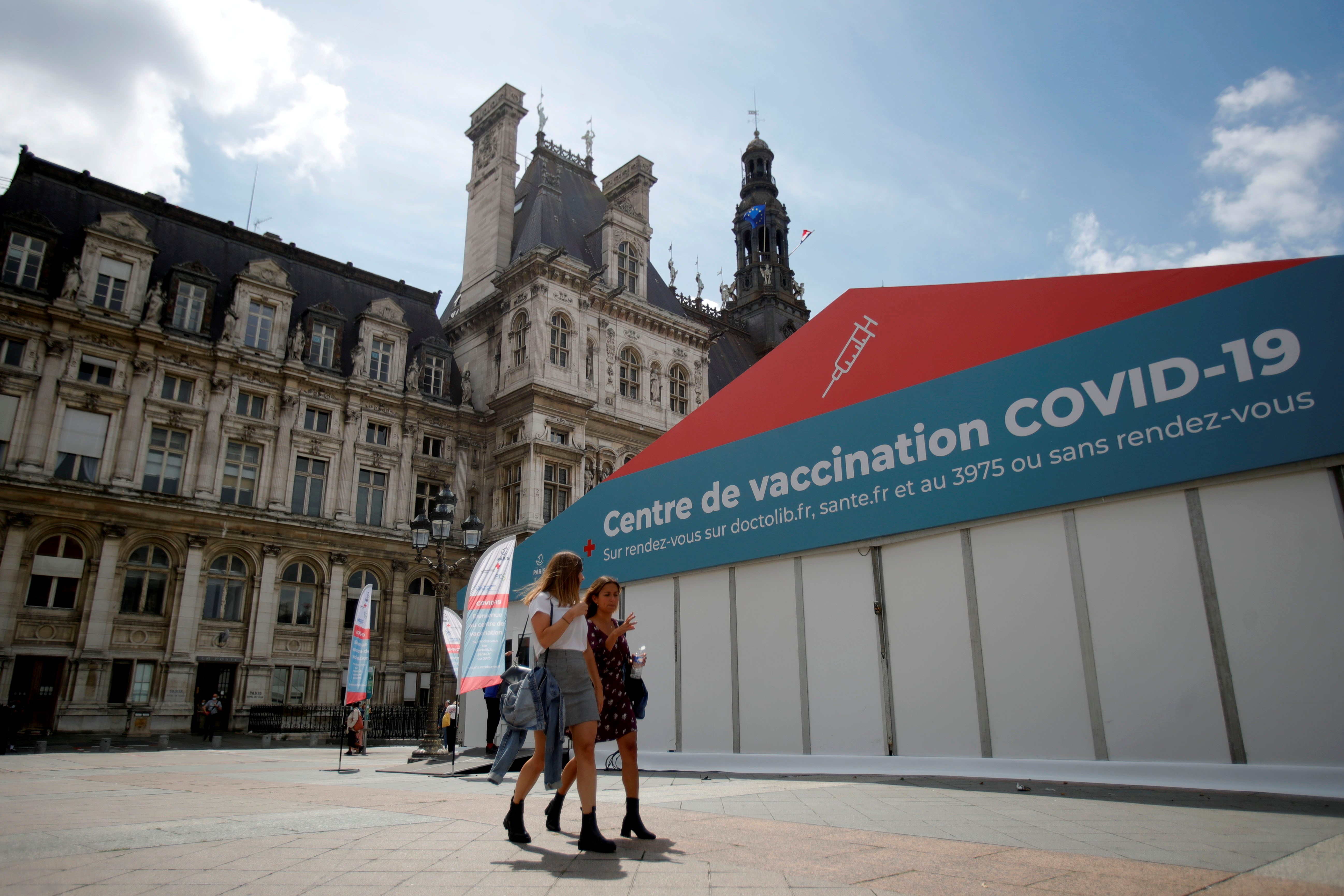 Women walk past a coronavirus disease (COVID-19) vaccination center installated in front of Paris town hall, France, July 7, 2021. REUTERS/Sarah Meyssonnier