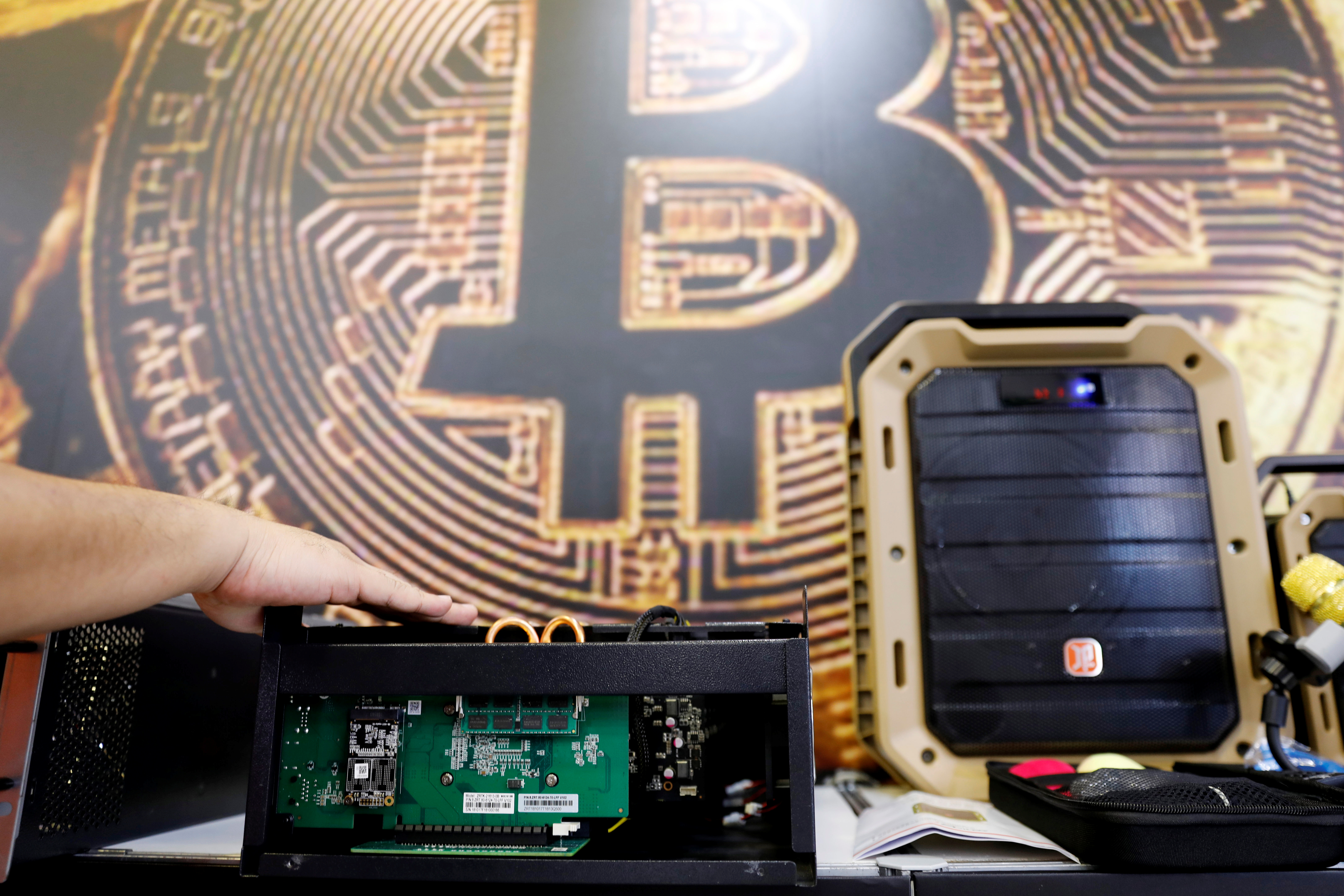 A cryptocurrency mining computer is seen in front of bitcoin logo during the annual Computex computer exhibition in Taipei, Taiwan June 5, 2018. REUTERS/Tyrone Siu - RC115698ECF0