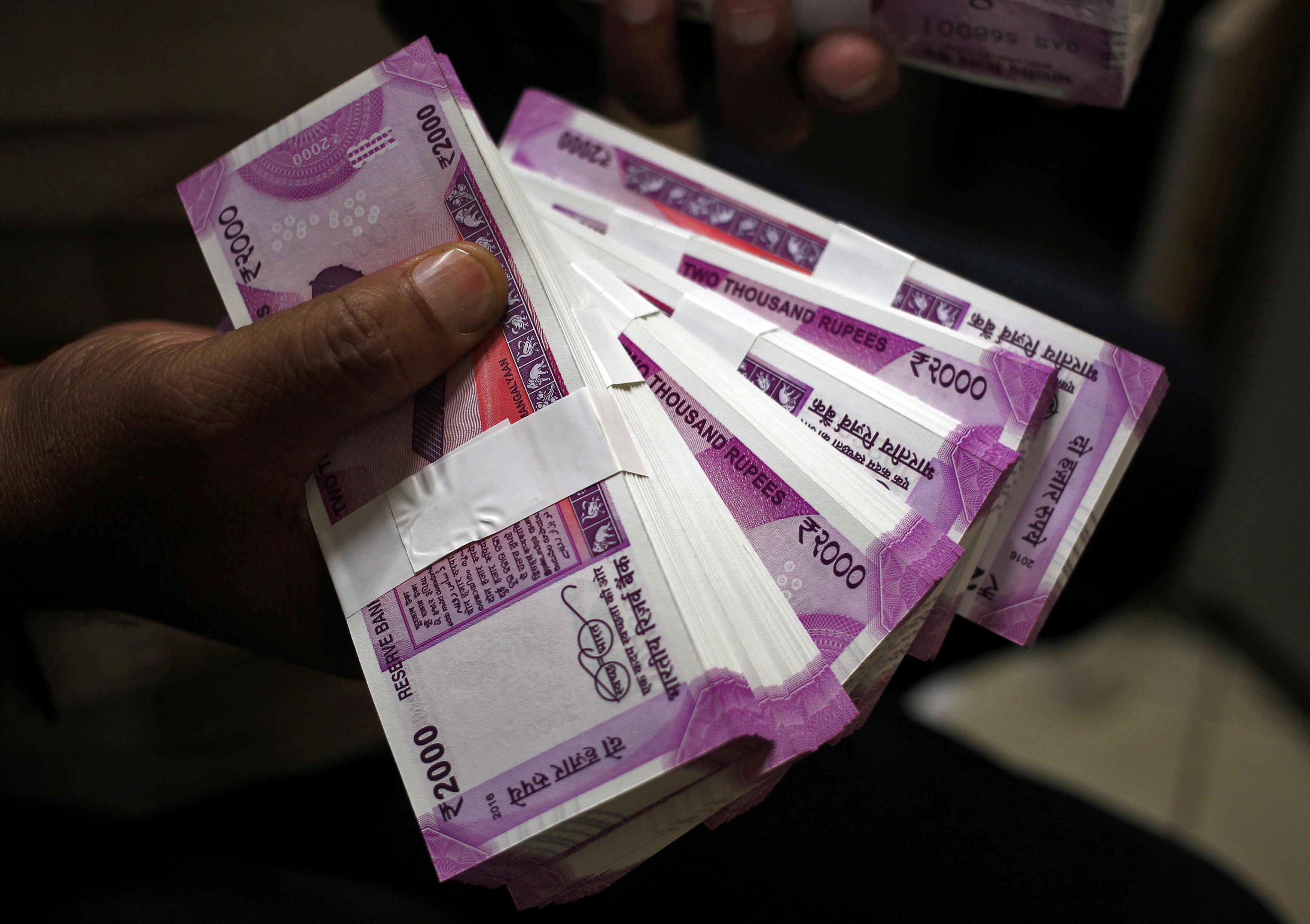 A cashier displays the new 2000 Indian rupee banknotes inside a bank in Jammu, November 15, 2016. REUTERS/Mukesh Gupta