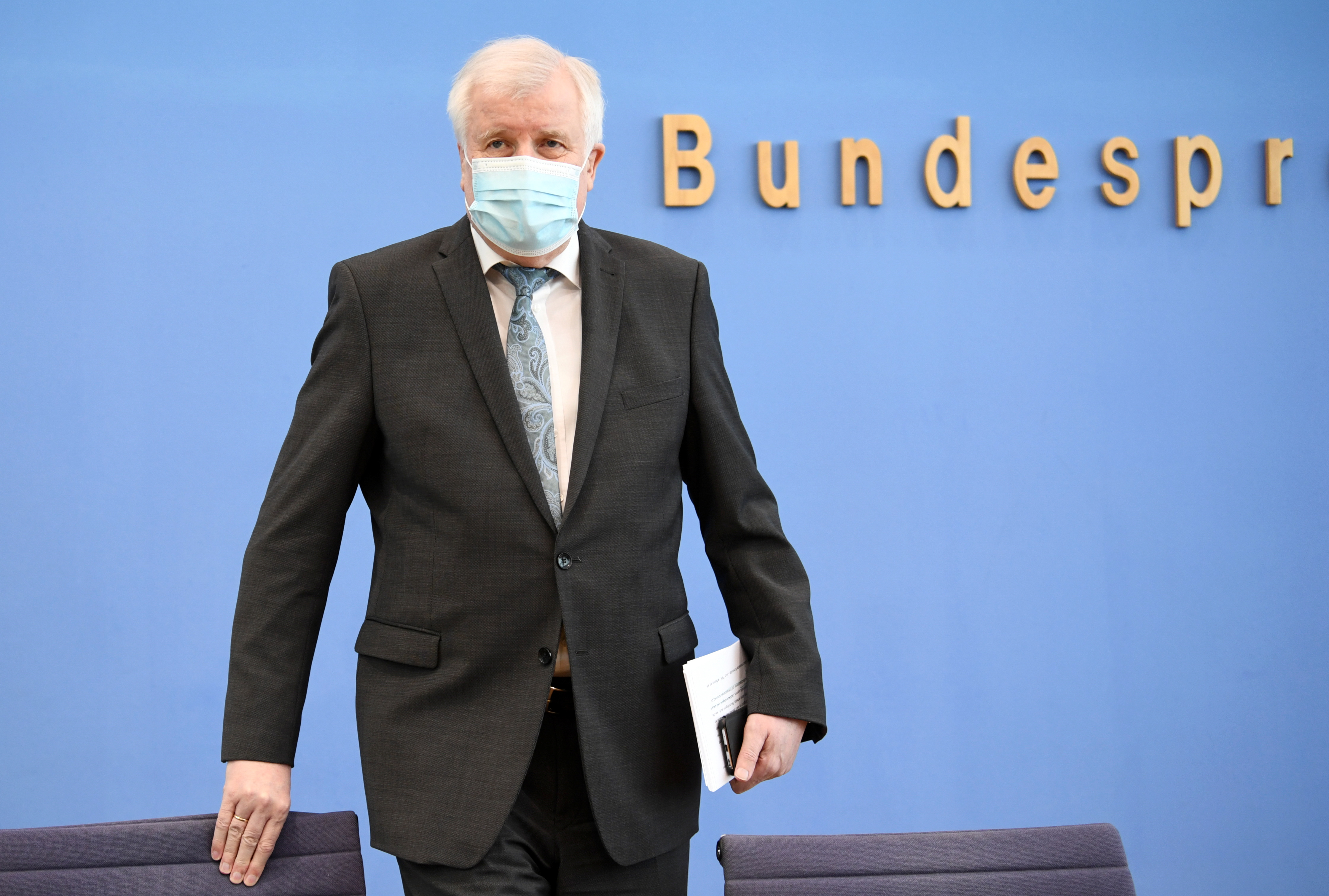 German Interior Minister Horst Seehofer takes off his mask before attending a news conference on politically motived crimes in Germany, in Berlin, Germany May 4, 2021. REUTERS/Annegret Hilse/Pool