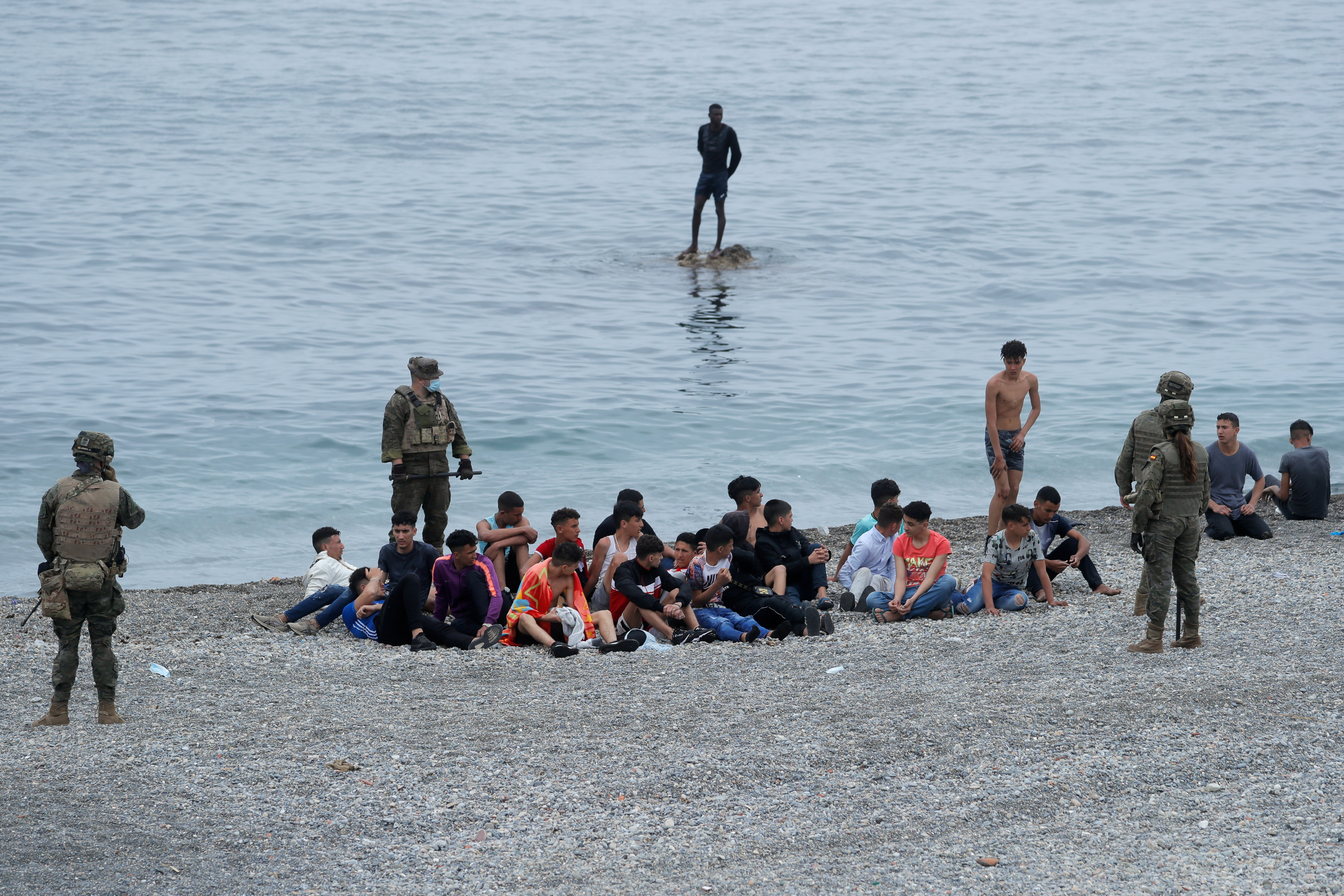 Spanish legionnaires stand around Moroccan citizens, after thousands of Moroccans swam across Spanish-Moroccan border on Monday, in Ceuta, Spain, May 18, 2021. REUTERS/Jon Nazca