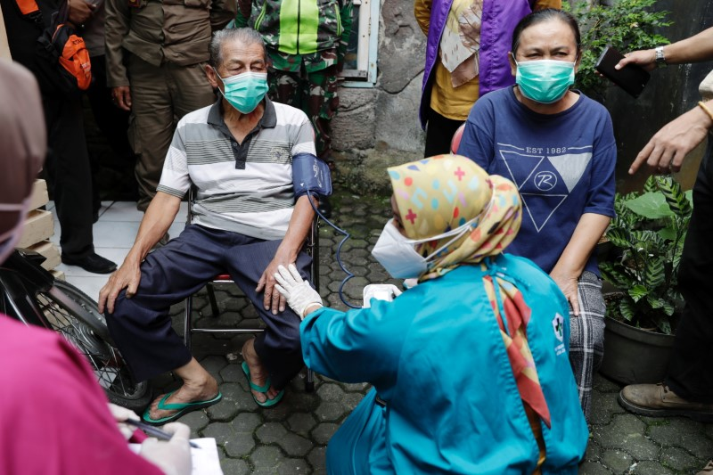 Inan Rustandi, 72, and his wife Neneng, 62, locals of Sindanglaya village, undergo health screening before receiving their first dose of a COVID-19 vaccine, outside their house during a door-to-door vaccination in Cianjur regency, West Java province, Indonesia, June 15, 2021. REUTERS/Willy Kurniawan