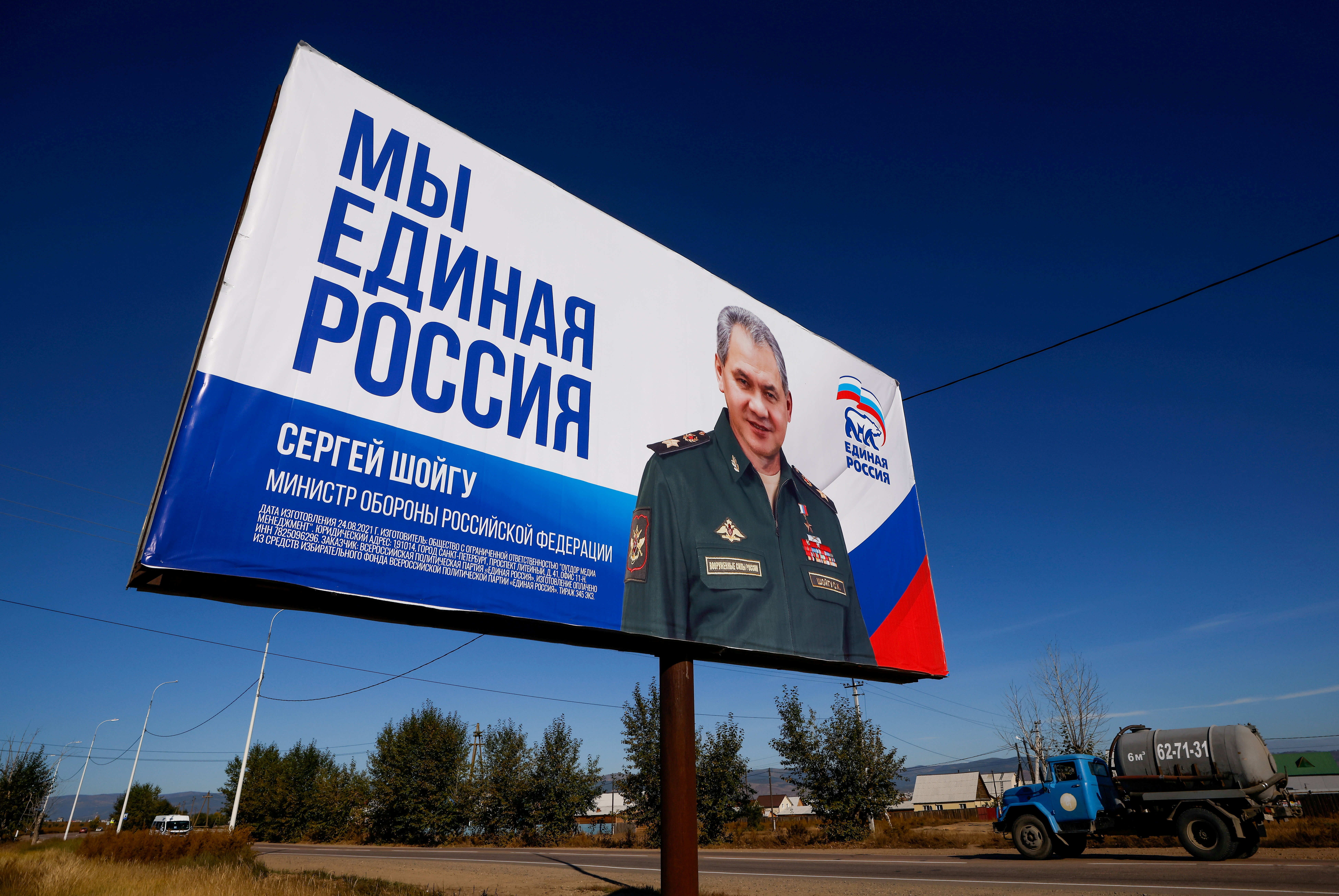 A truck drives past a campaign poster of the United Russia political party ahead of the Russian parliamentary and regional election outside Ulan-Ude, Buryatia republic, Russia September 16, 2021. REUTERS/Maxim Shemetov/File Photo