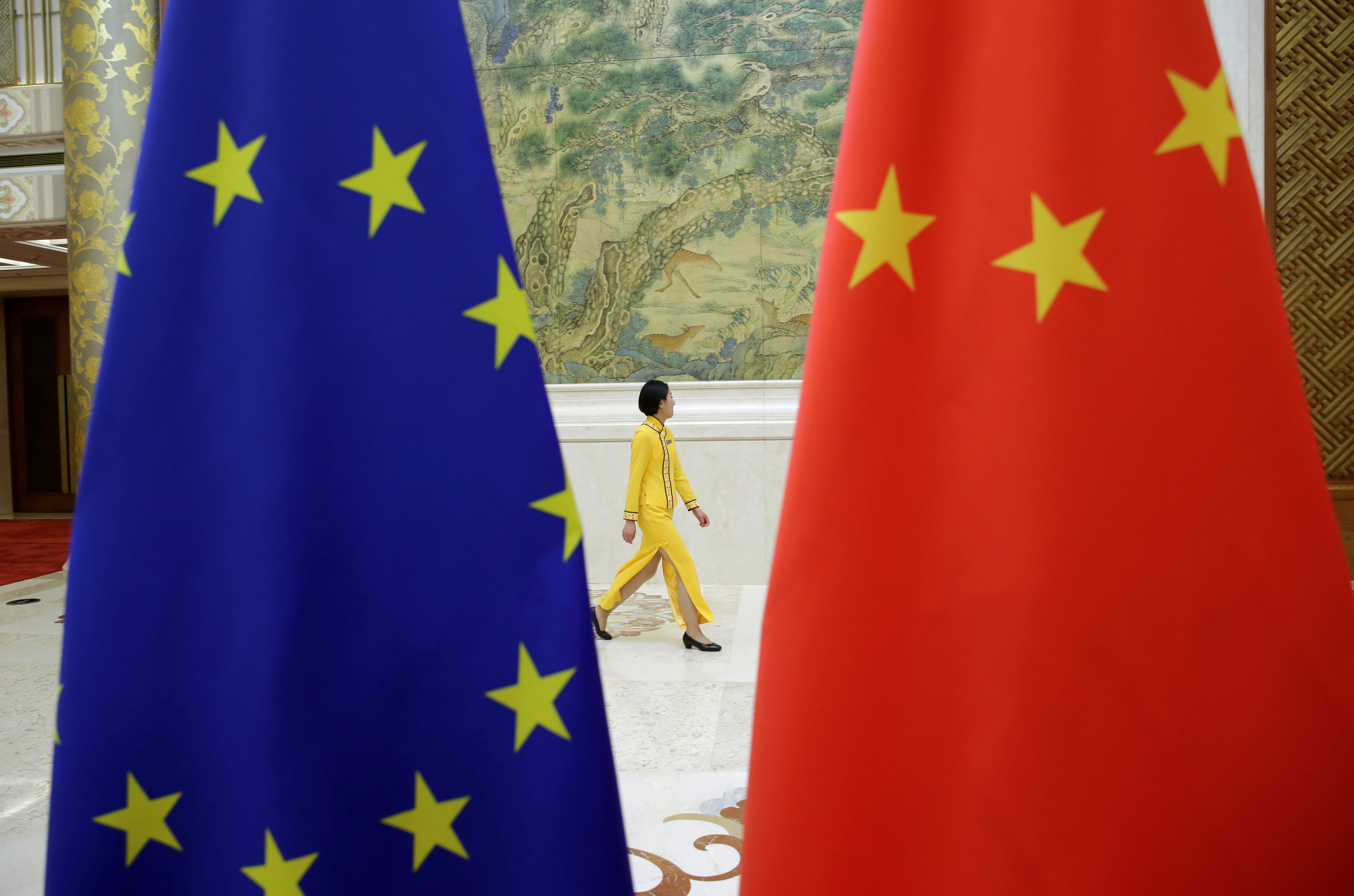 An attendant walks past EU and China flags ahead of the EU-China High-level Economic Dialogue at Diaoyutai State Guesthouse in Beijing, China June 25, 2018. REUTERS/Jason Lee