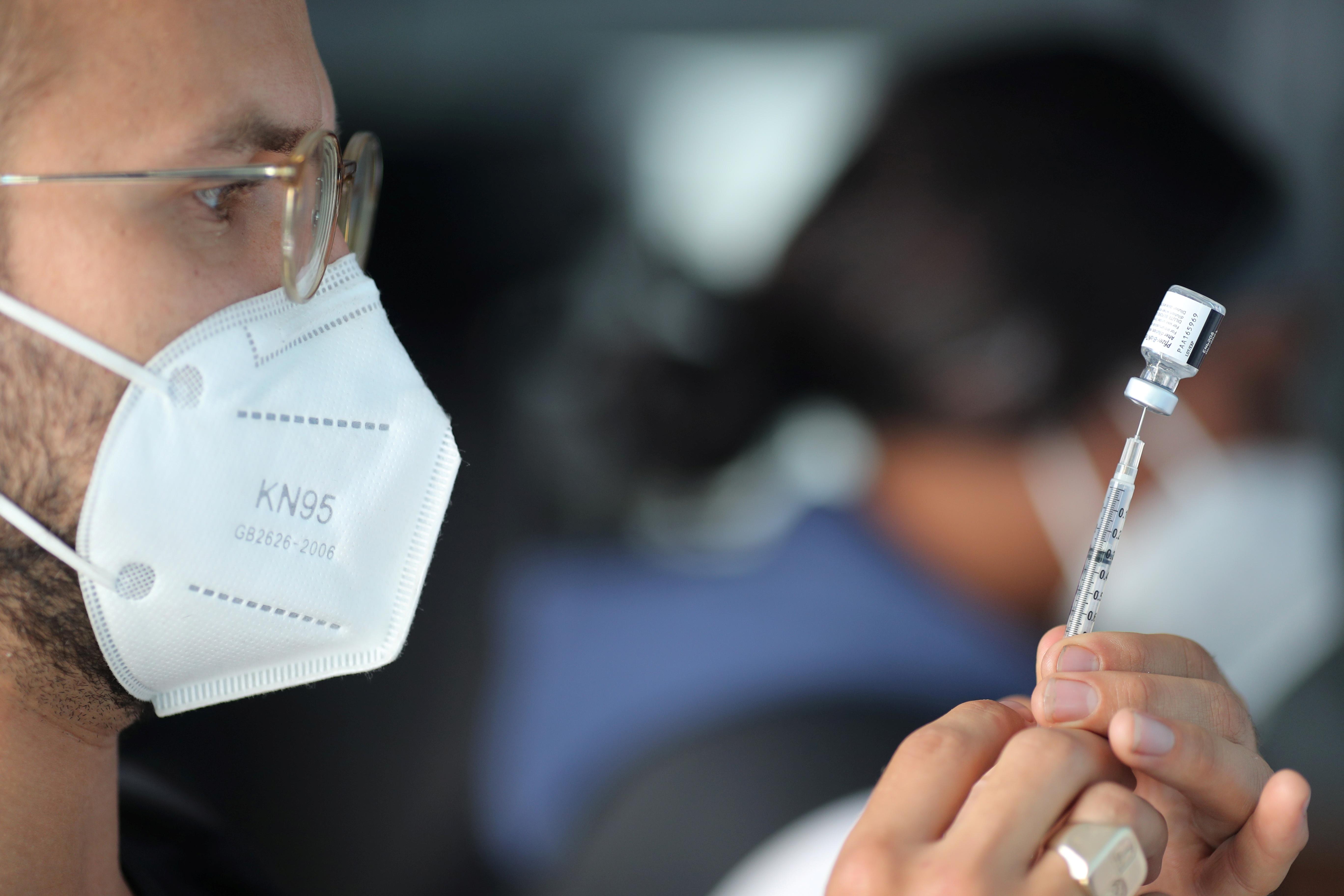 EMT Lenny Fernandez chuẩn bị chủng ngừa bệnh do Pfizer coronavirus (COVID-19) tại một ổ tiêm chủng lưu động cho các công nhân chế biến thực phẩm thiết yếu tại Rose & Shore, Inc., ở Vernon, Los Angeles, California, Hoa Kỳ, ngày 17 tháng 3 năm 2021. REUTERS / Lucy Nicholson
