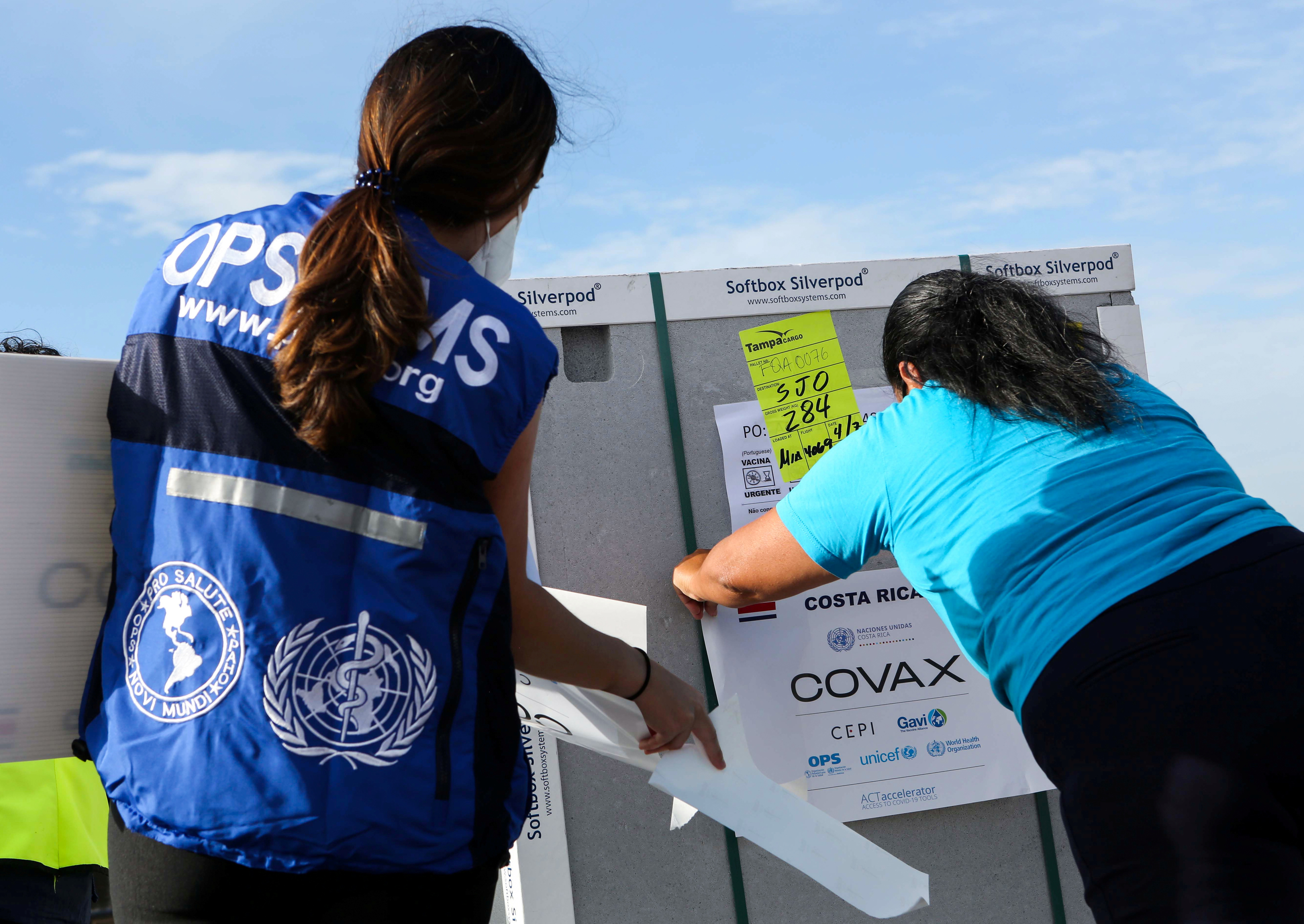 People mark a container holding doses of the AstraZeneca's vaccine against the coronavirus disease (COVID-19) that arrived under the COVAX scheme, in Alajuela, on the outskirts of San Jose, Costa Rica April 7, 2021. REUTERS/Mayela Lopez
