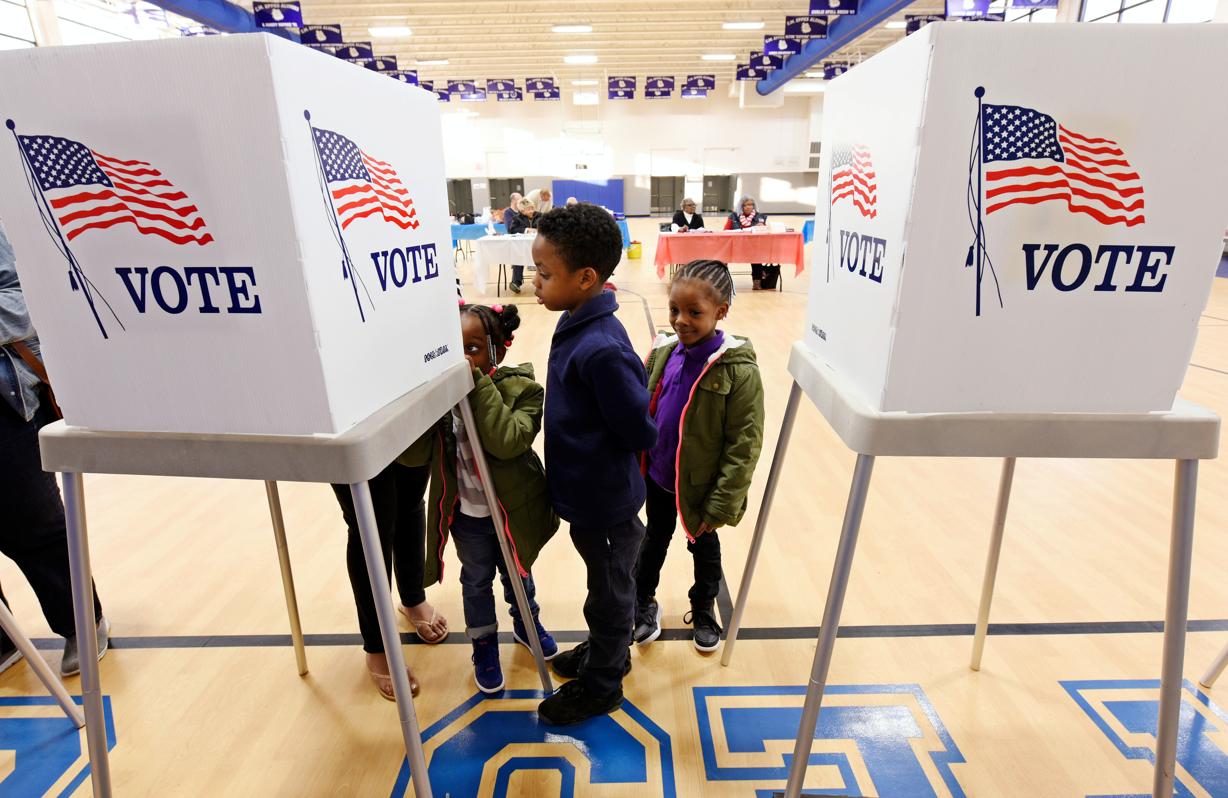 Children watch their mother vote during the U.S. general election in Greenville, North Carolina, U.S. on November 8, 2016.  REUTERS/Jonathan Drake