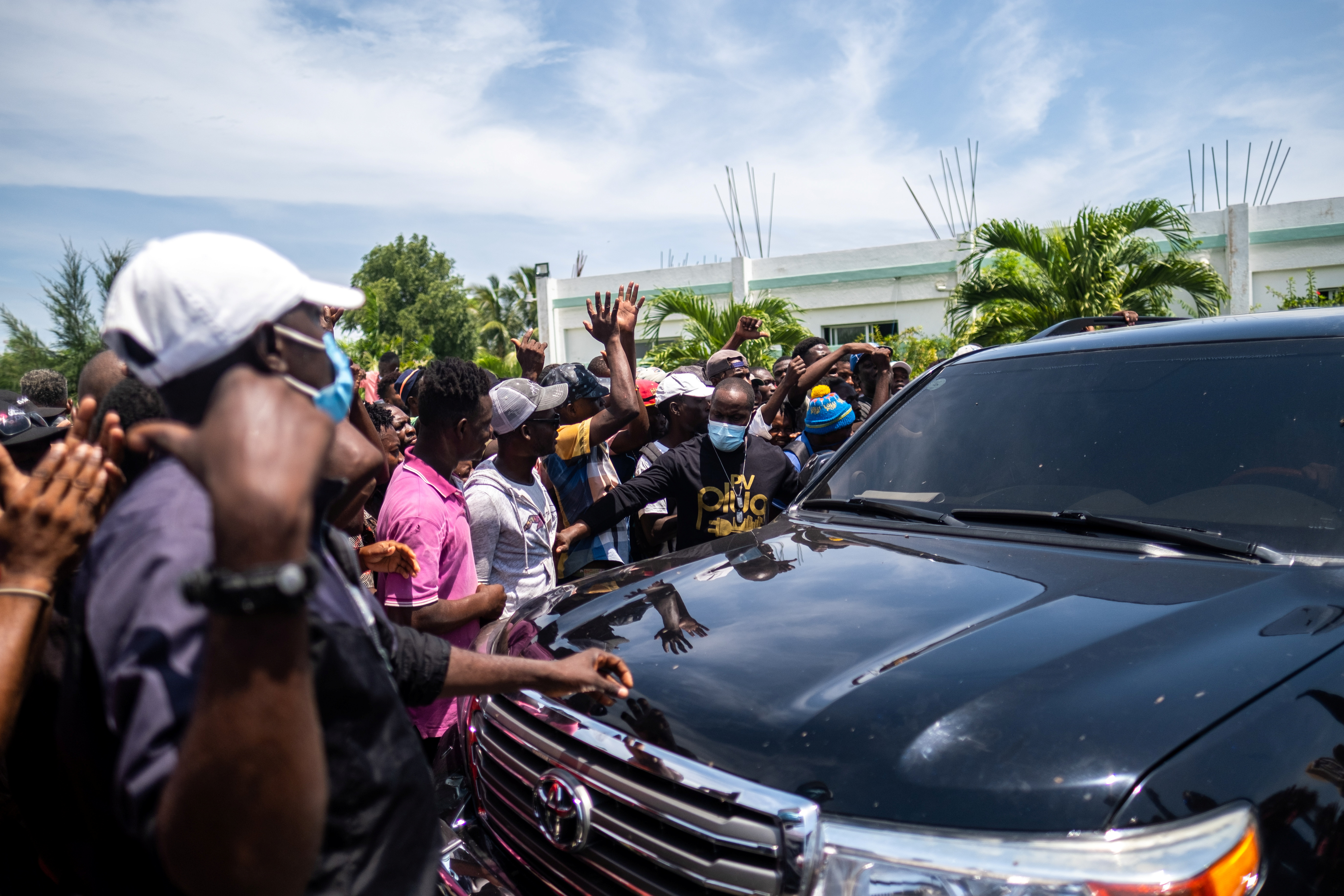 Followers of former Haitian President Michel Martelly follow his vehicle after his visit to the OFATMA hospital in Les Cayes, Haiti August 20, 2021. REUTERS/Ricardo Arduengo