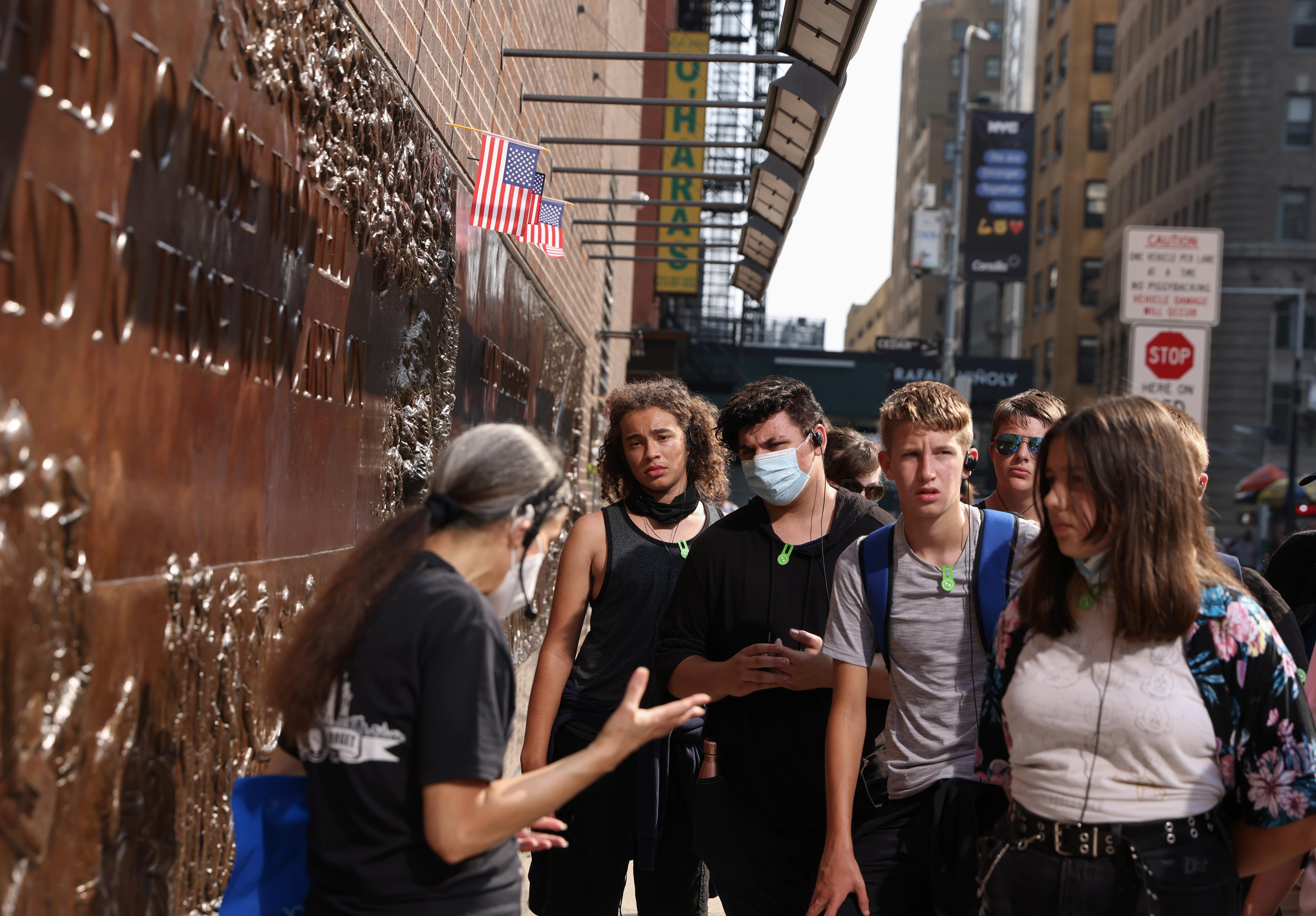 (L-R) Students Zavion Turner, Elijah Johnson, Colin Dukes, and Gillian Rodriguez-Lentz, listen to docent Joan Mastropaolo explain a memorial outside the 9/11 Tribute Museum in New York City, U.S., August 26, 2021. REUTERS/Caitlin Ochs