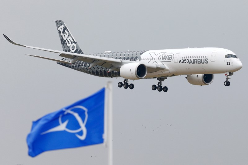 An Airbus A350 jetliner flies over Boeing flags as it lands after a flying display during the 51st Paris Air Show at Le Bourget airport near Paris, June 15, 2015. REUTERS/Pascal Rossignol/File Photo