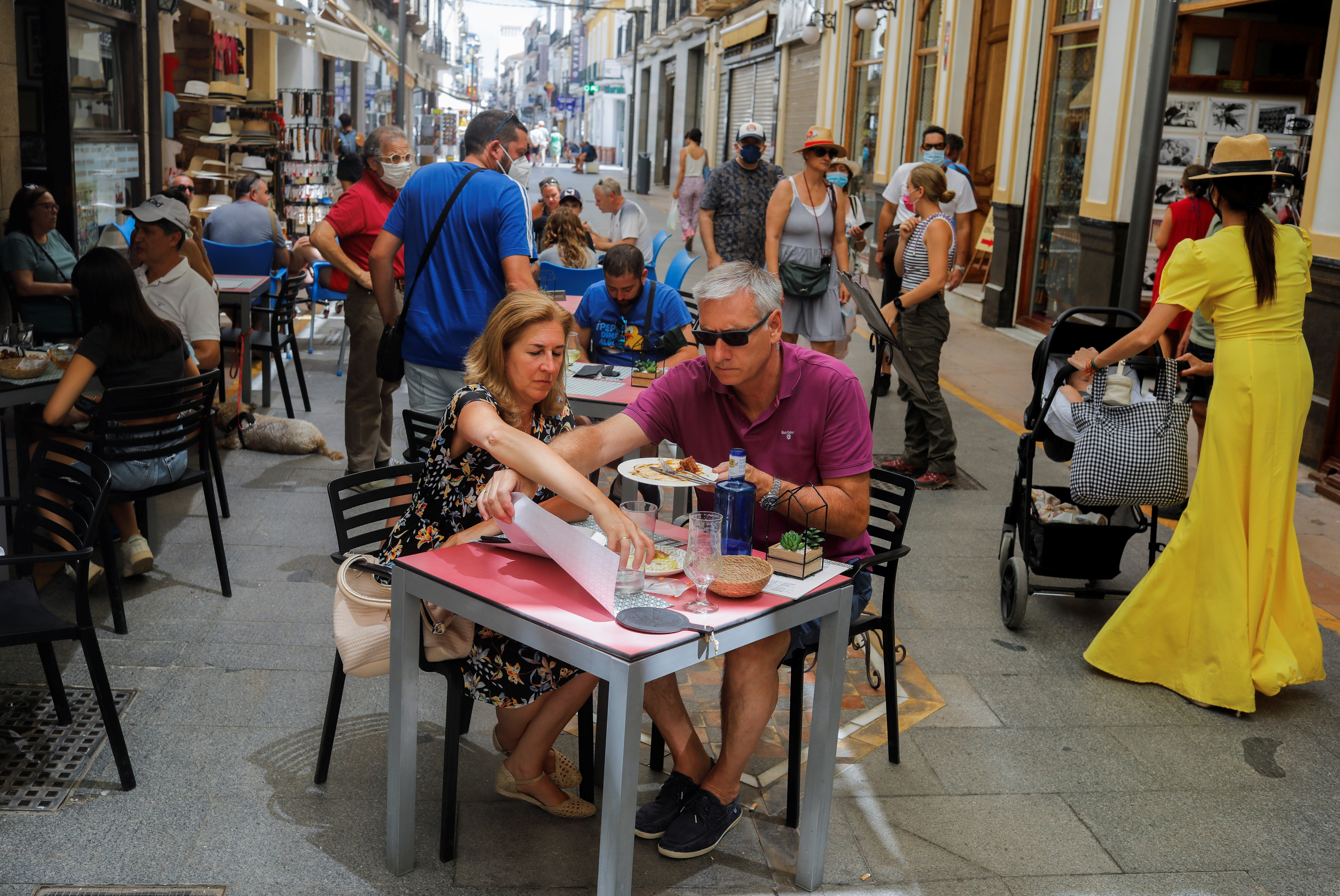 Tourists sit at a bar's terrace amid the coronavirus disease (COVID-19) outbreak in Ronda, southern Spain, August 3, 2021. REUTERS/Jon Nazca