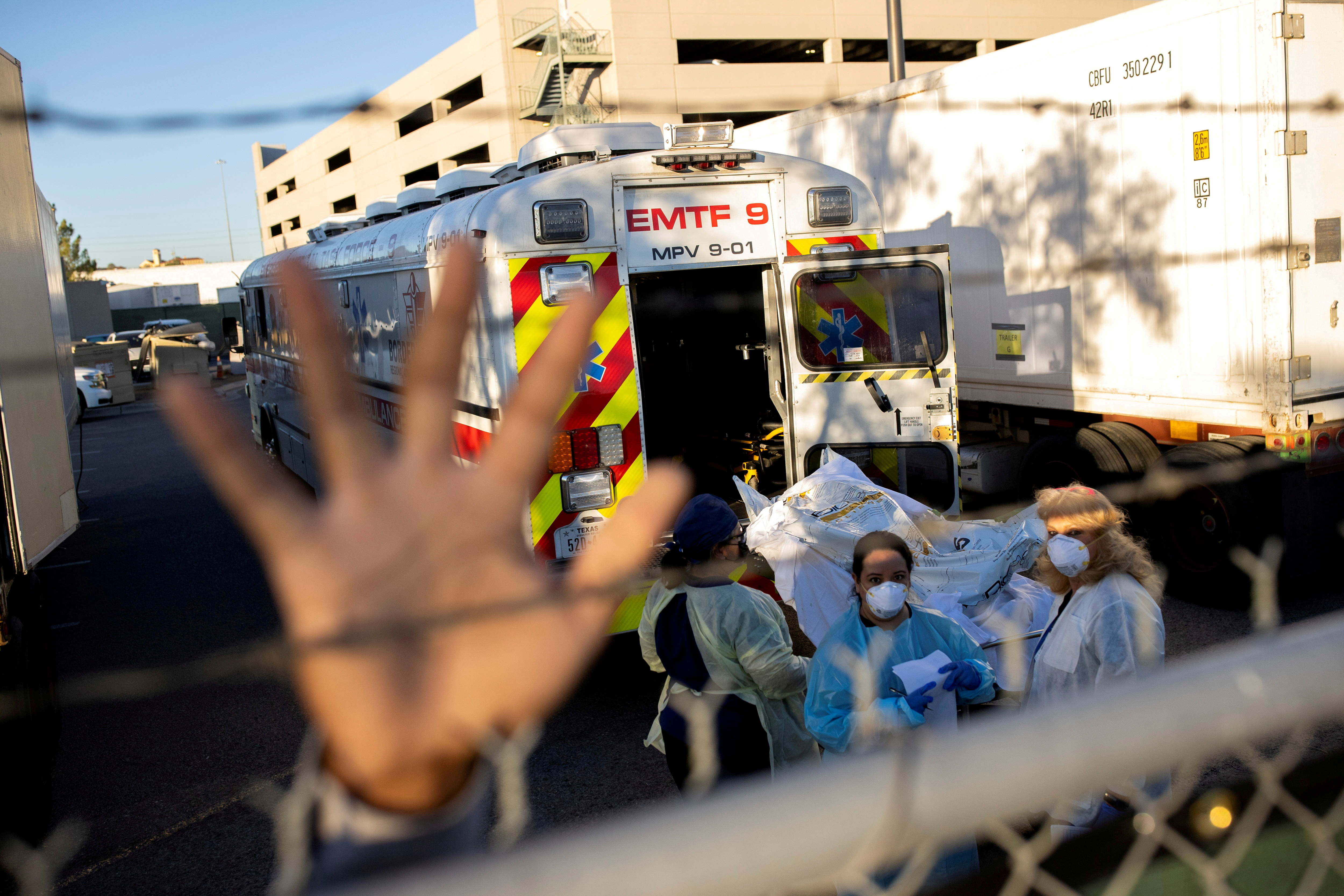 An El Paso County Sheriff's Officer tries to block photographs from being taken as bodies are moved to refrigerated trailers, deployed during a surge of coronavirus disease (COVID-19) deaths, outside the County of El Paso Medical Examiner's Office in El Paso, Texas, U.S. November 16, 2020.  REUTERS/Ivan Pierre Aguirre