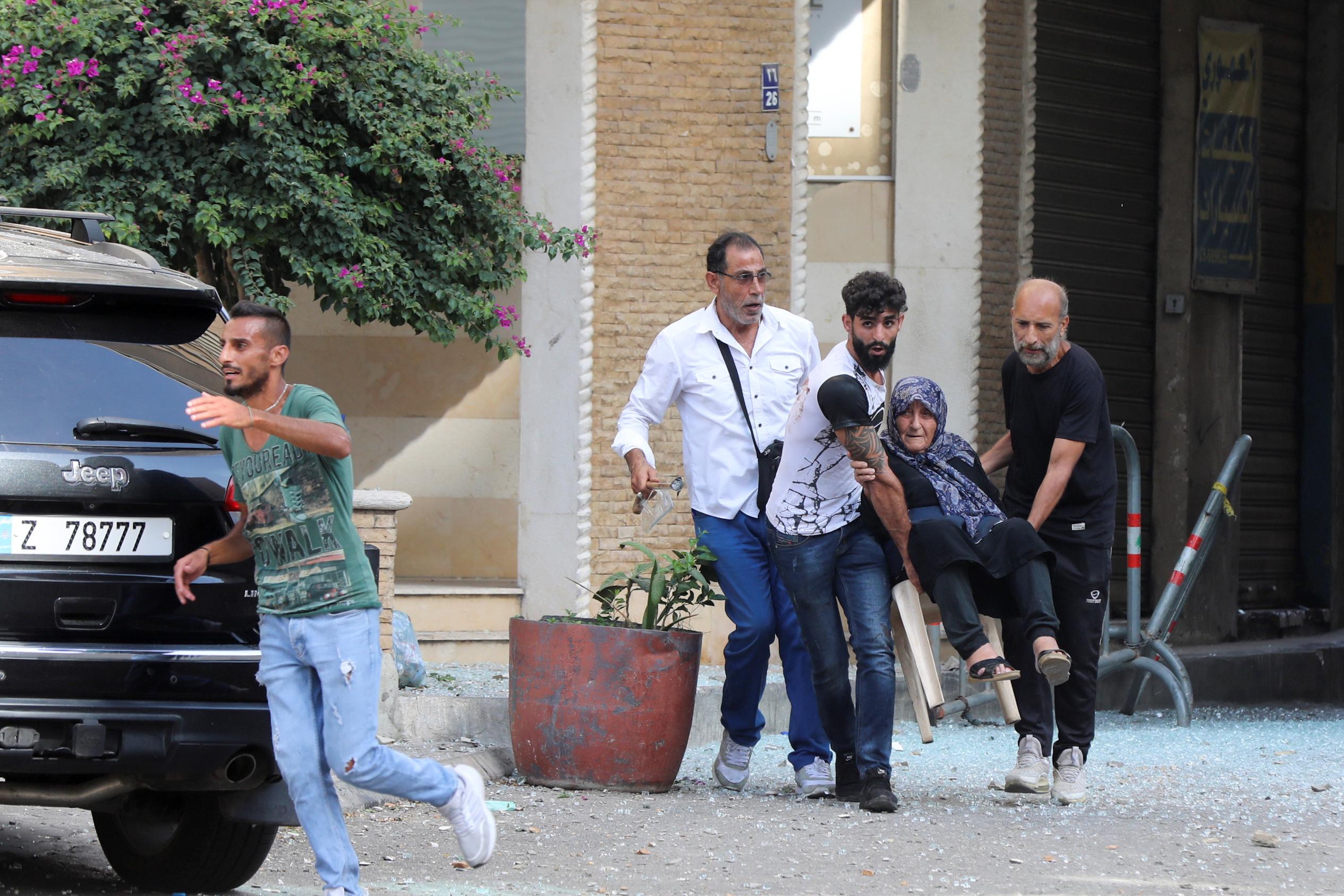 Men help evacuate an elderly woman after gunfire erupted, in Beirut, Lebanon October 14, 2021.  REUTERS/Mohamed Azakir