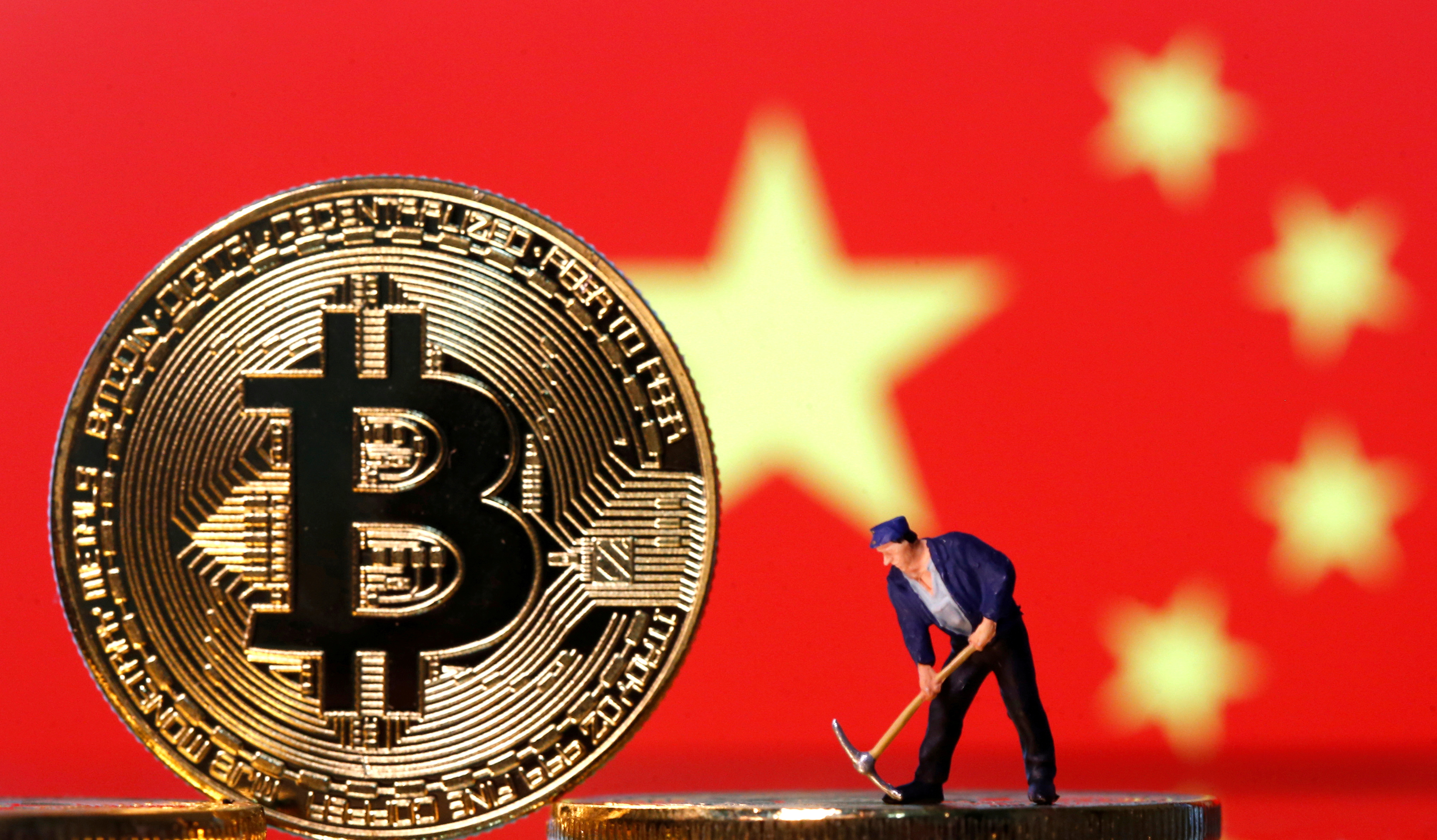 A small toy figurine is seen on representations of the Bitcoin virtual currency displayed in front of an image of China's flag in this illustration picture, April 9, 2019. REUTERS/Dado Ruvic/Illustration