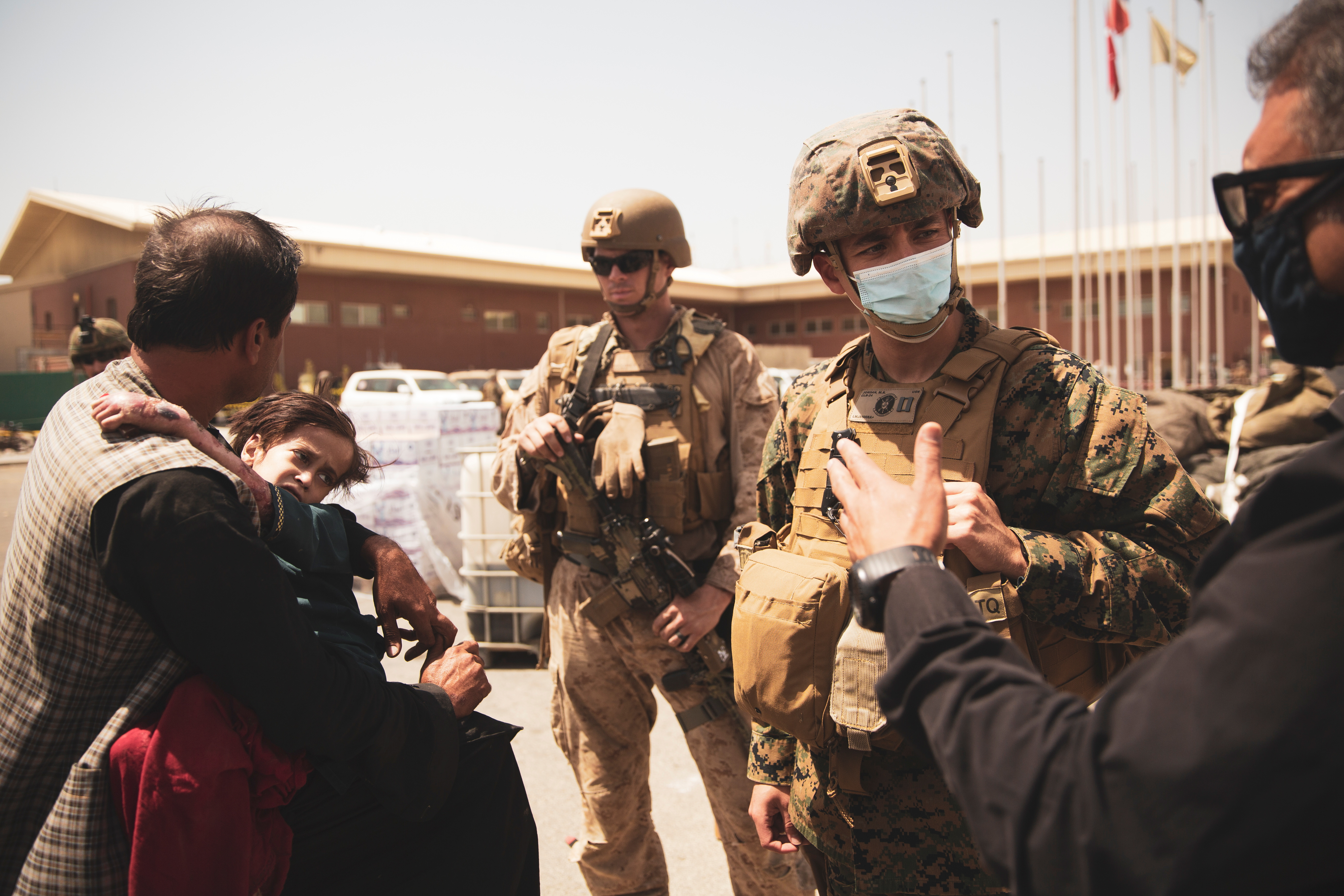 A U.S. Navy medical surgeon with the 24th Marine Expeditionary Unit (MEU) talks to an interpreter as he provides medical assistance to a family during an evacuation at Hamid Karzai International Airport, Kabul, Afghanistan, August 21, 2021. Picture taken August 21, 2021.  U.S. Marine Corps/Staff Sgt. Victor Mancilla/Handout via REUTERS/Files