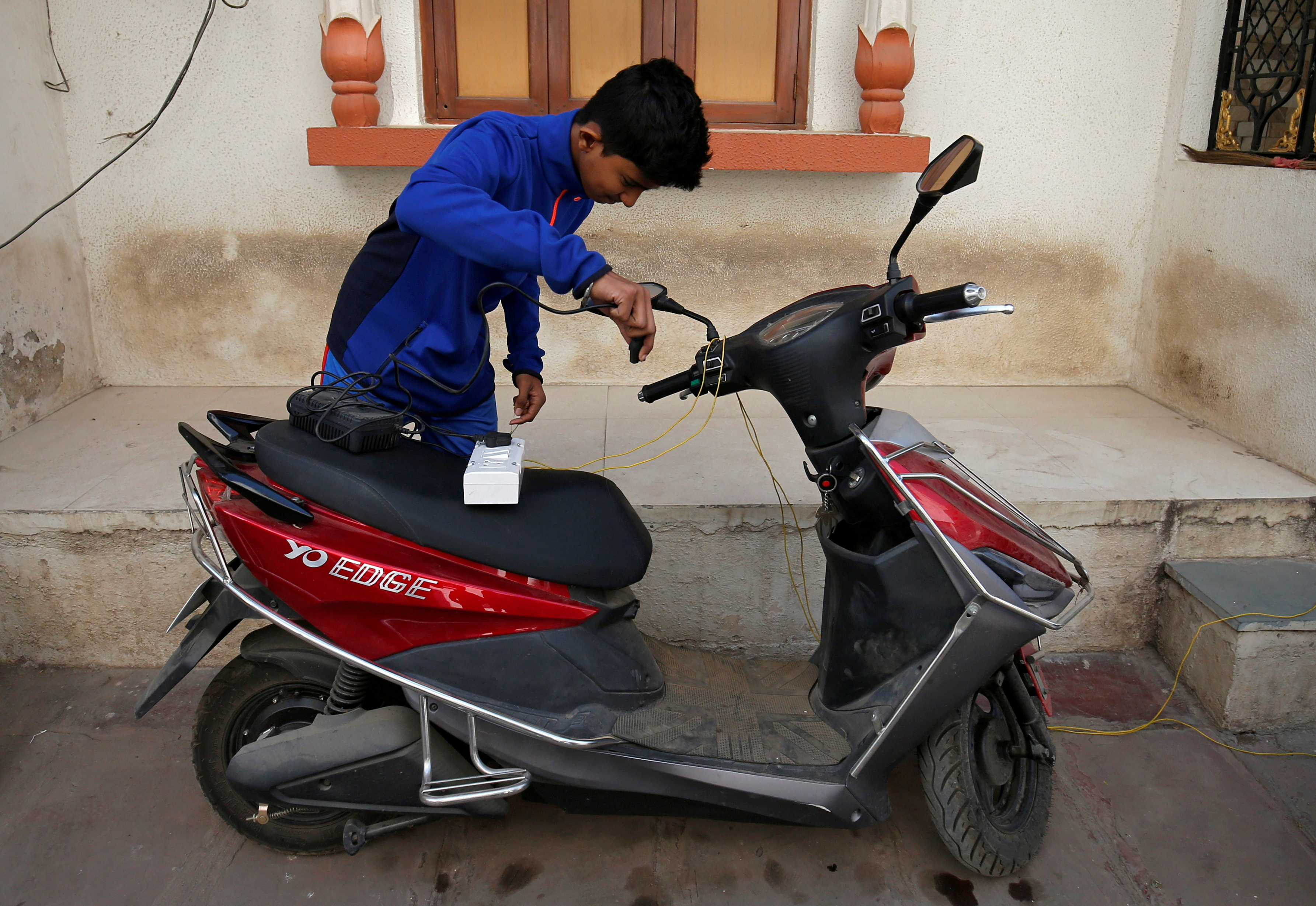 A boy prepares to recharge his electric scooter outside his home in Ahmedabad, India, December 30, 2018. Picture taken December 30, 2018. REUTERS/Amit Dave/File Photo