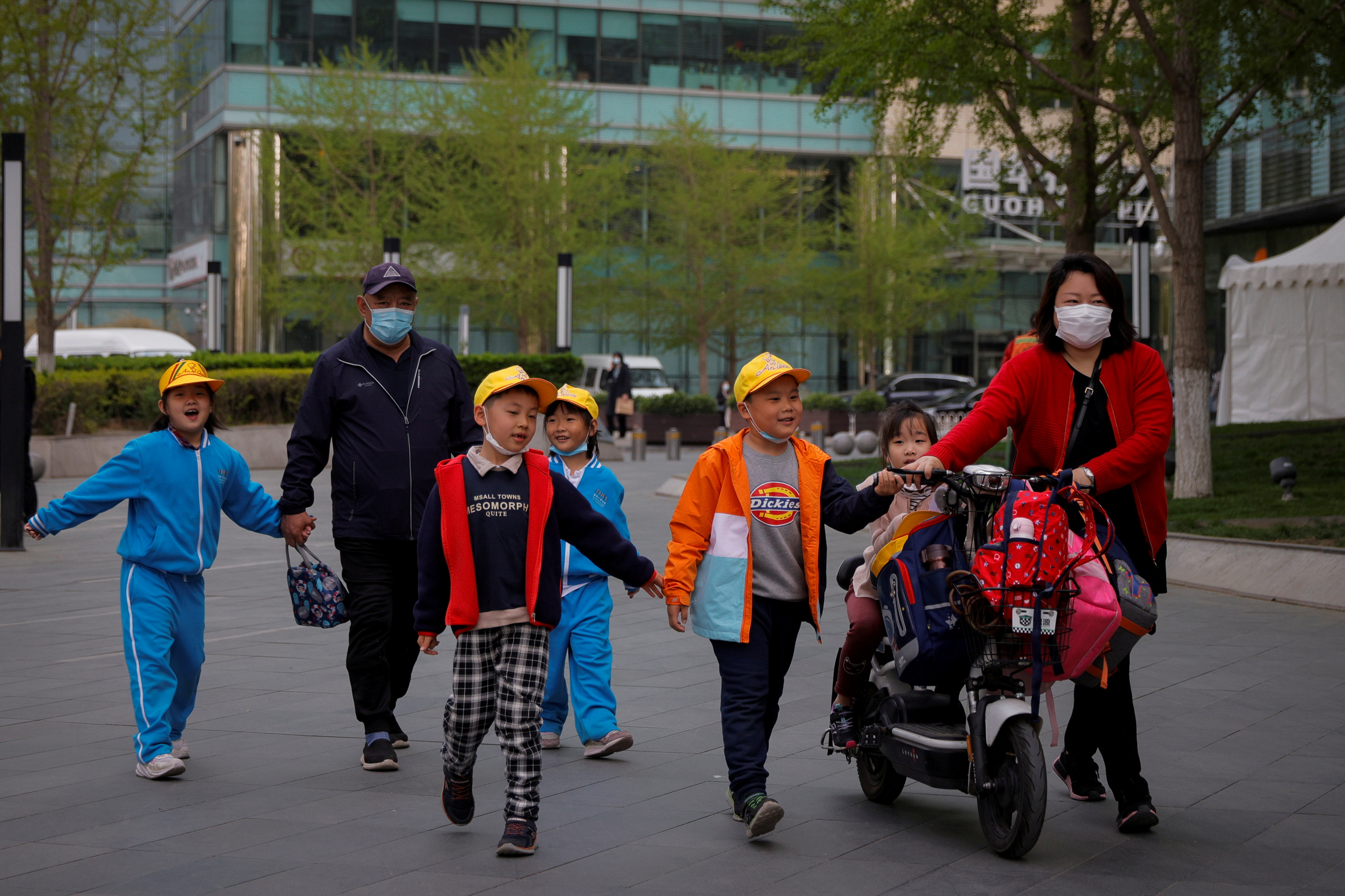 People pick up children from a school in Beijing, China, April 6, 2021. REUTERS/Thomas Peter