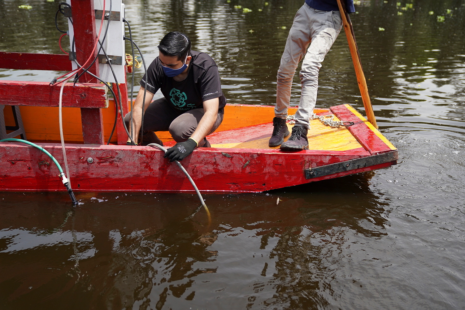 """A member of a team of researchers from the Center for Research and Advanced Studies (Cinvestav), who developed a method that converts solar energy into photovoltaic energy that activates a pump that sends """"nanobubbles"""" into the water, tests a water system at a trajinera boat as part of a project to clean the polluted waters at the canals of Xochimilco, in Mexico City, Mexico August 20, 2021. REUTERS/Toya Sarno Jordan"""