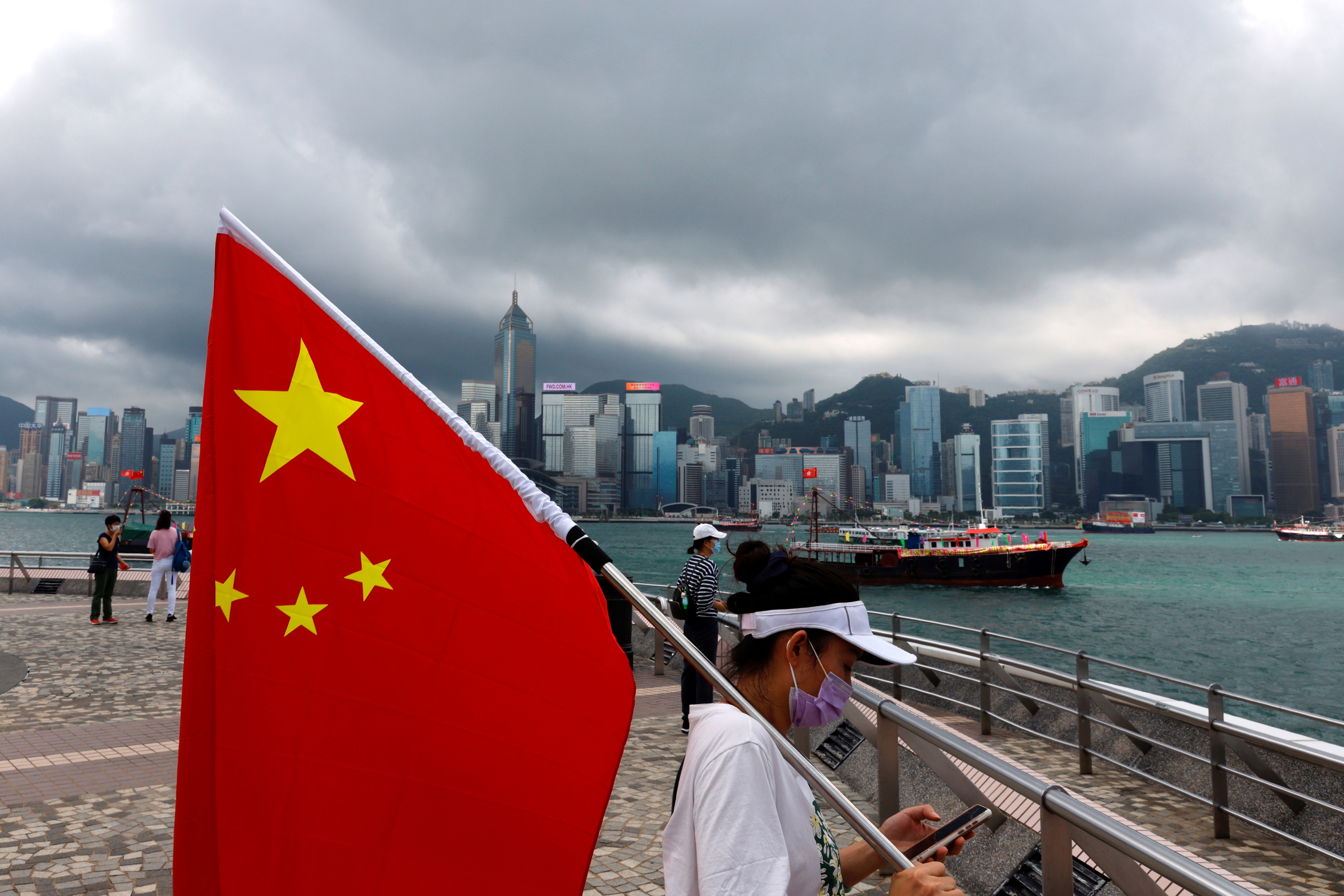A pro-China supporter holds a Chinese flag to celebrate the 24th anniversary of the former British colony's return to Chinese rule, on the 100th founding anniversary of the Communist Party of China, in Hong Kong, China July 1, 2021. REUTERS/Tyrone Siu