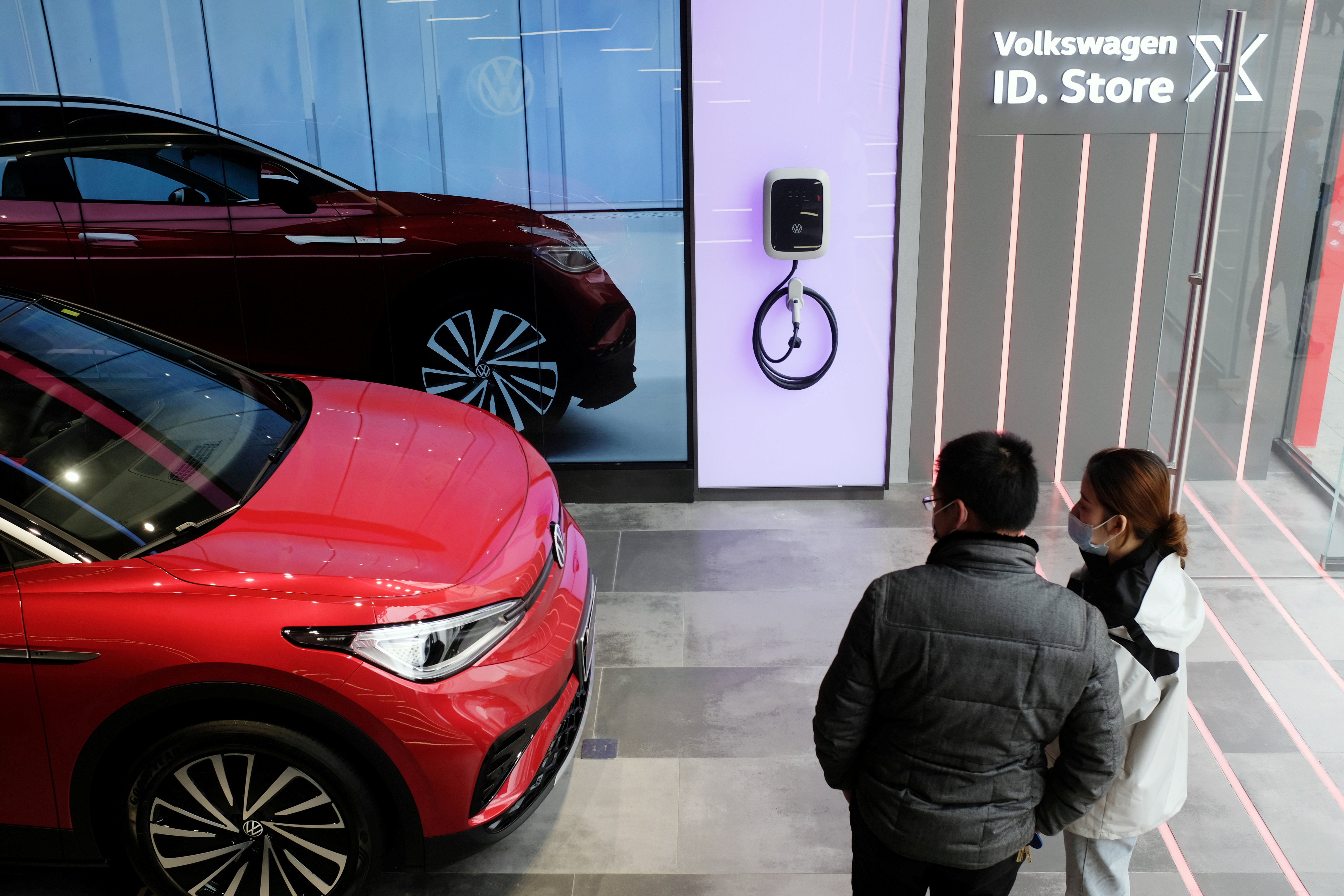 People check a Volkswagen ID.4 X electric vehicle displayed inside an ID. Store X showroom of SAIC Volkswagen in Chengdu, Sichuan province, China January 10, 2021. REUTERS/Yilei Sun/File Photo