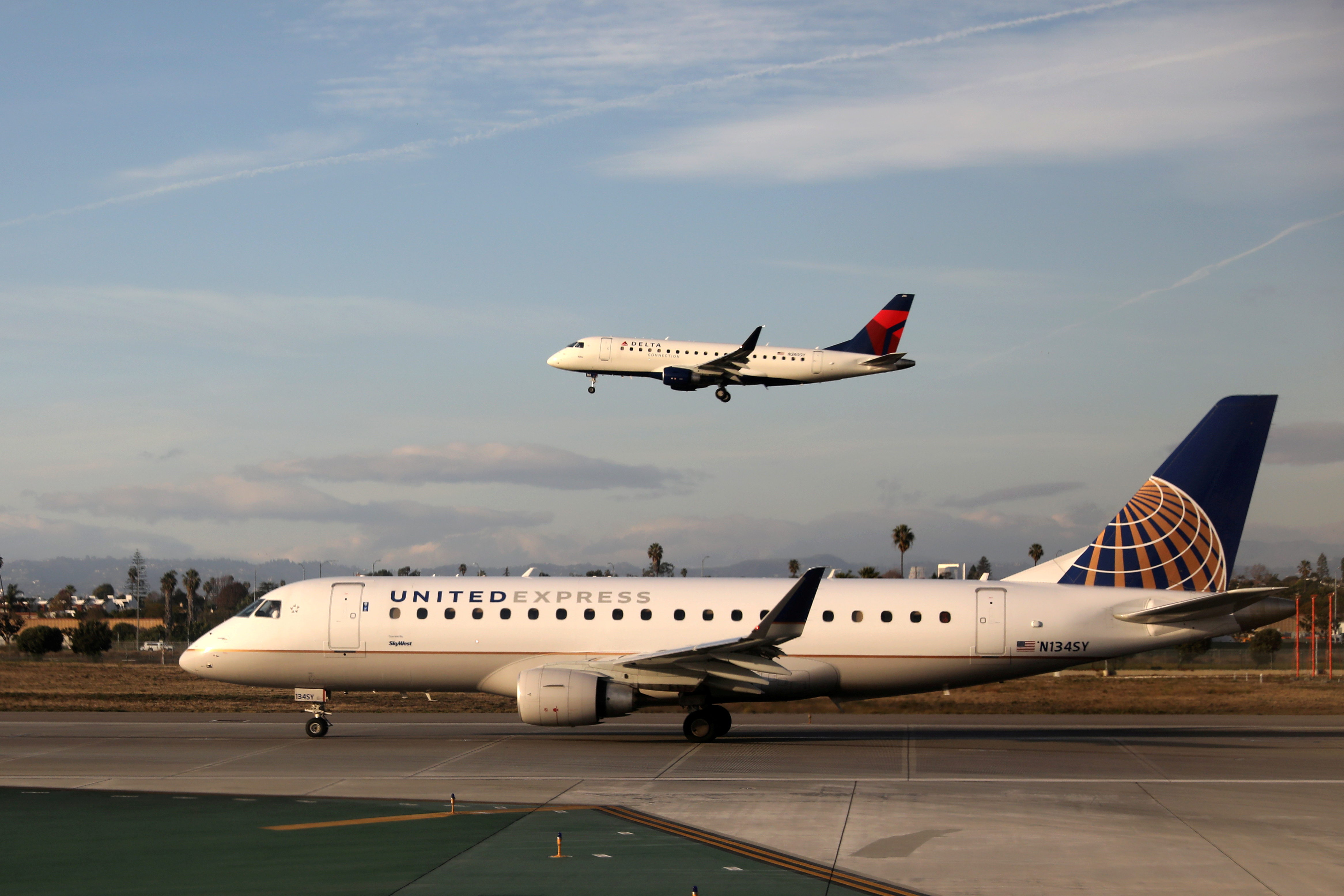A Delta Connection Embraer ERJ-175LR plane lands as a United Express Embraer ERJ-175LR plane waits to take off at LAX airport in Los Angeles, California U.S. January 10, 2018. REUTERS/Lucy Nicholson