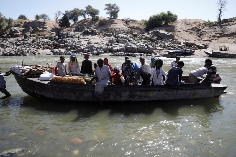 Ethiopians fleeing from the Tigray region arrive by boat to Sudan after crossing a river between the two countries, near the Hamdayet refugee transit camp, Sudan, December 1, 2020. Picture taken December 1, 2020.      REUTERS/Baz Ratner/File Photo