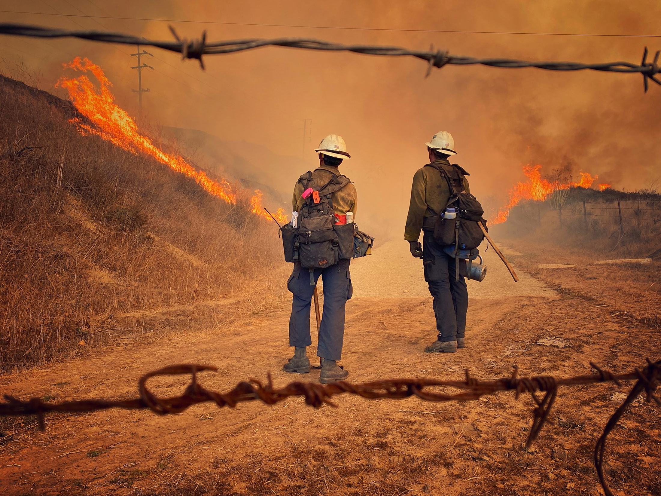 Santa Barbara County Fire Hand Crew members burn off pockets of grass in the Alisal Fire along northbound Highway 101 north of Arroyo Hondo Canyon, California, U.S. October 12, 2021. Mike Eliason/SBCo FD/Handout via REUTERS