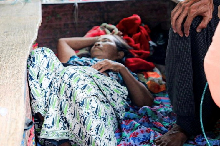 Relative sits with a coronavirus disease (COVID-19) patient in the town of Kale, Sagaing Region, Myanmar, May 31, 2021. Picture taken May 31, 2021. REUTERS/Stringer/File Photo