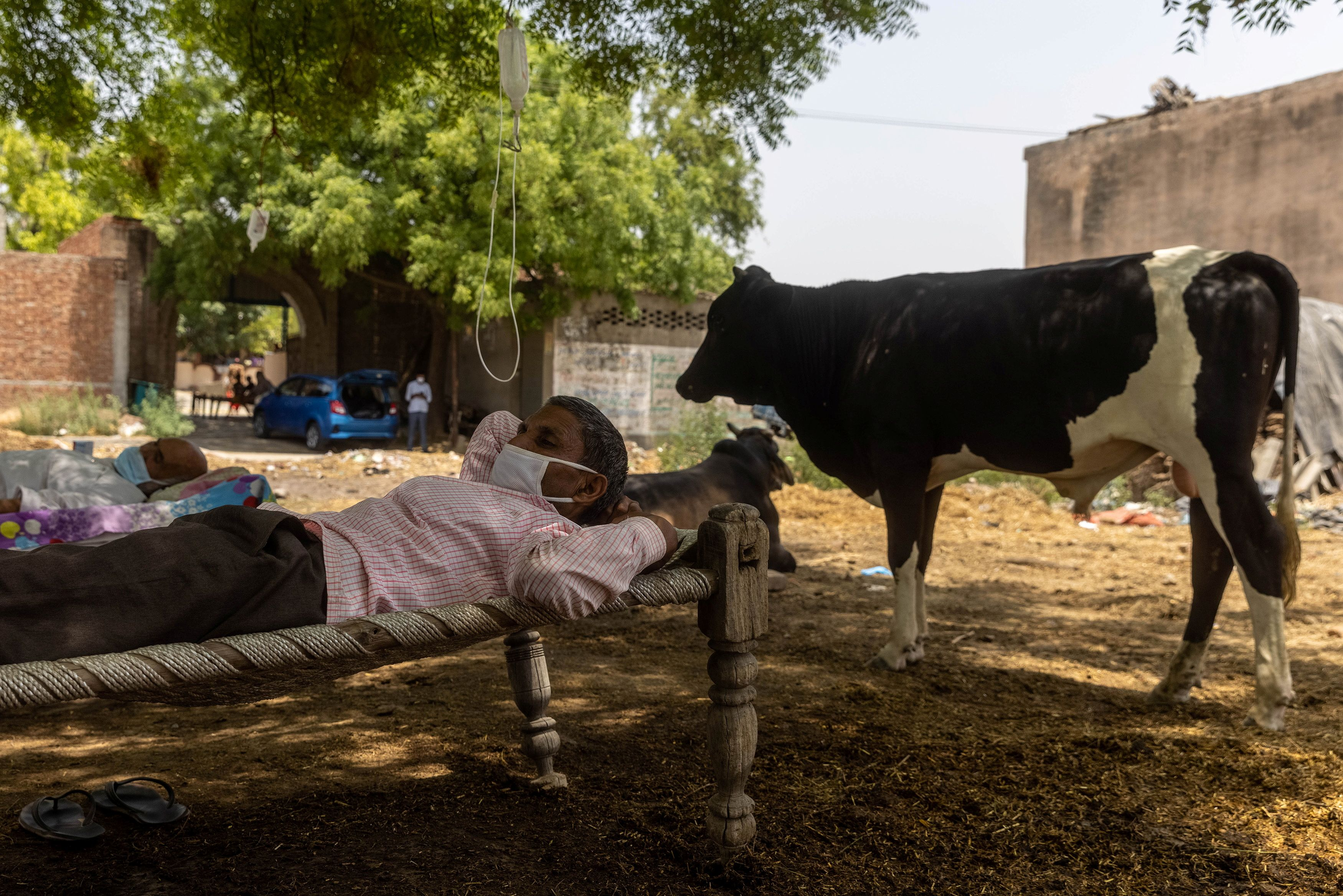 Roshan Lal, 48, a villager with a breathing difficulty rests in a cot as he receives treatment at a makeshift open-air clinic, amidst the spread of the coronavirus disease (COVID-19), in Mewla Gopalgarh village, in Jewar district, in the northern state of Uttar Pradesh, India, May 16, 2021. Picture taken May 16, 2021. REUTERS/Danish Siddiqui