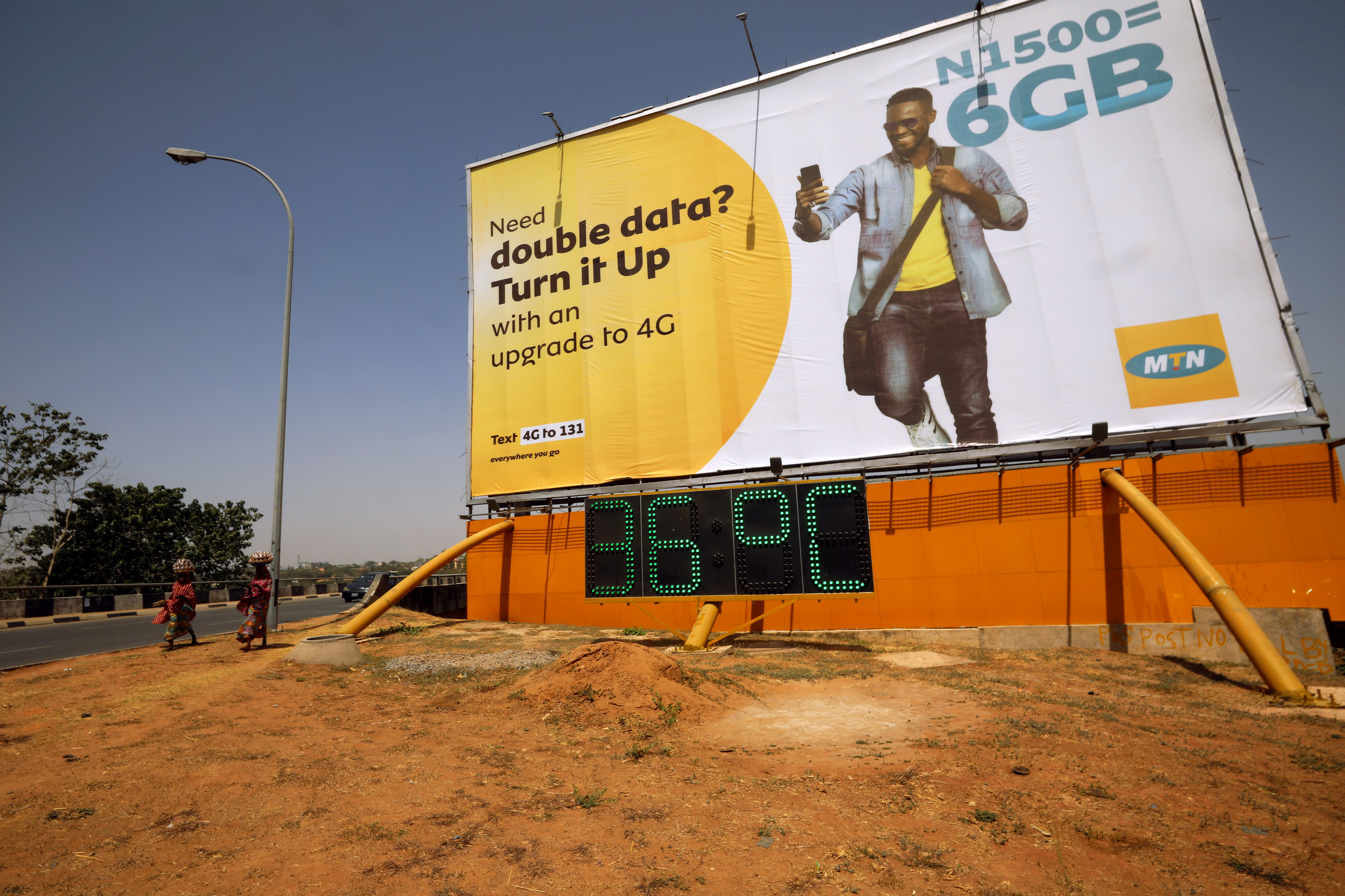 People walk past an advertising billboard for MTN telecommunication company in Abuja, Nigeria February 24, 2020. REUTERS/Afolabi Sotunde/File Photo