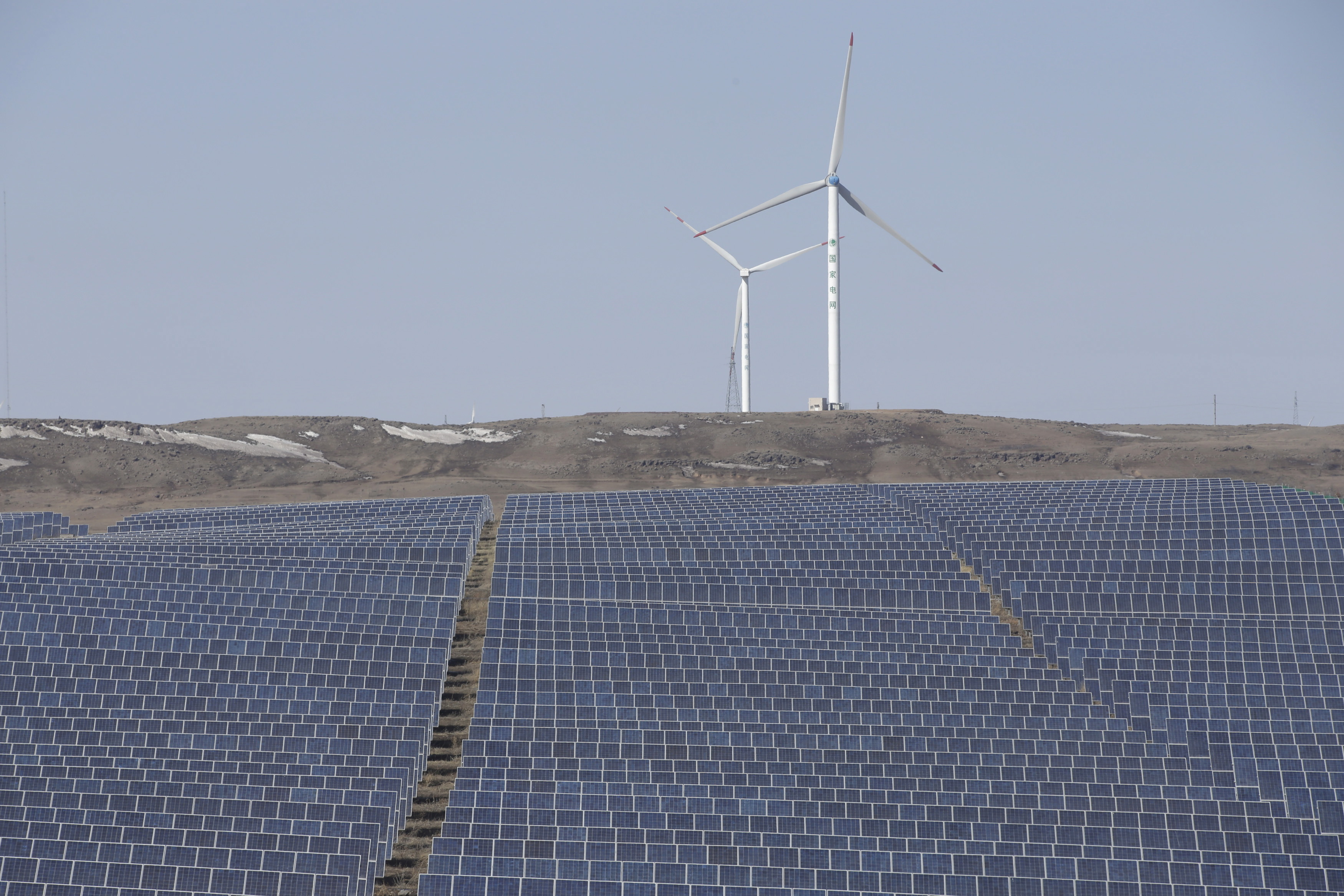 Wind turbines and solar panels are seen at a wind and solar energy storage and transmission power station from State Grid Corporation of China, in Zhangjiakou of Hebei province, China, March 18, 2016. REUTERS/Jason Lee/Files