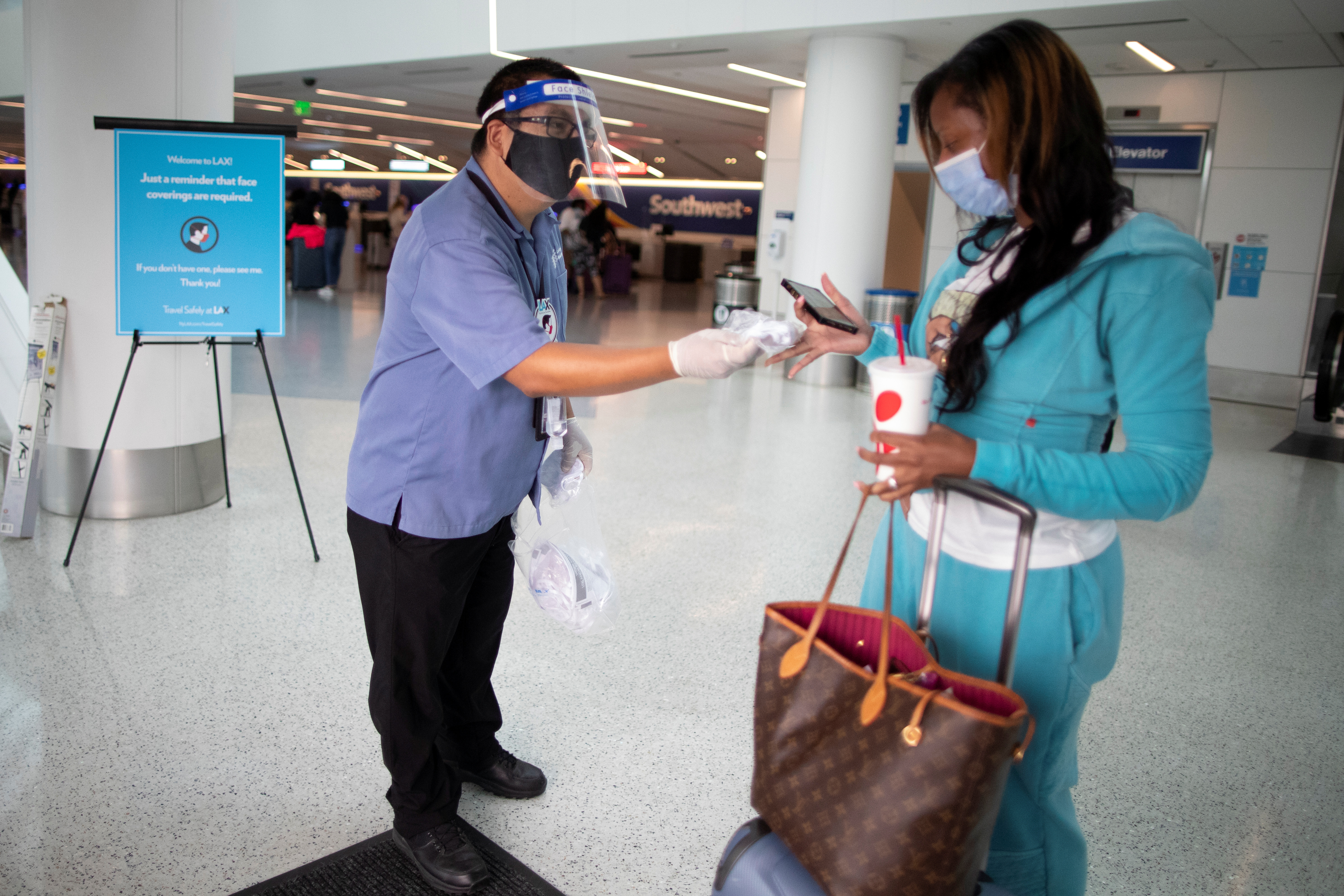 Travel Safely Ambassador Carlos Hernandez hands out a face masks to an airline passenger at LAX airport in Los Angeles, California, U.S., August 4, 2020. REUTERS/Lucy Nicholson