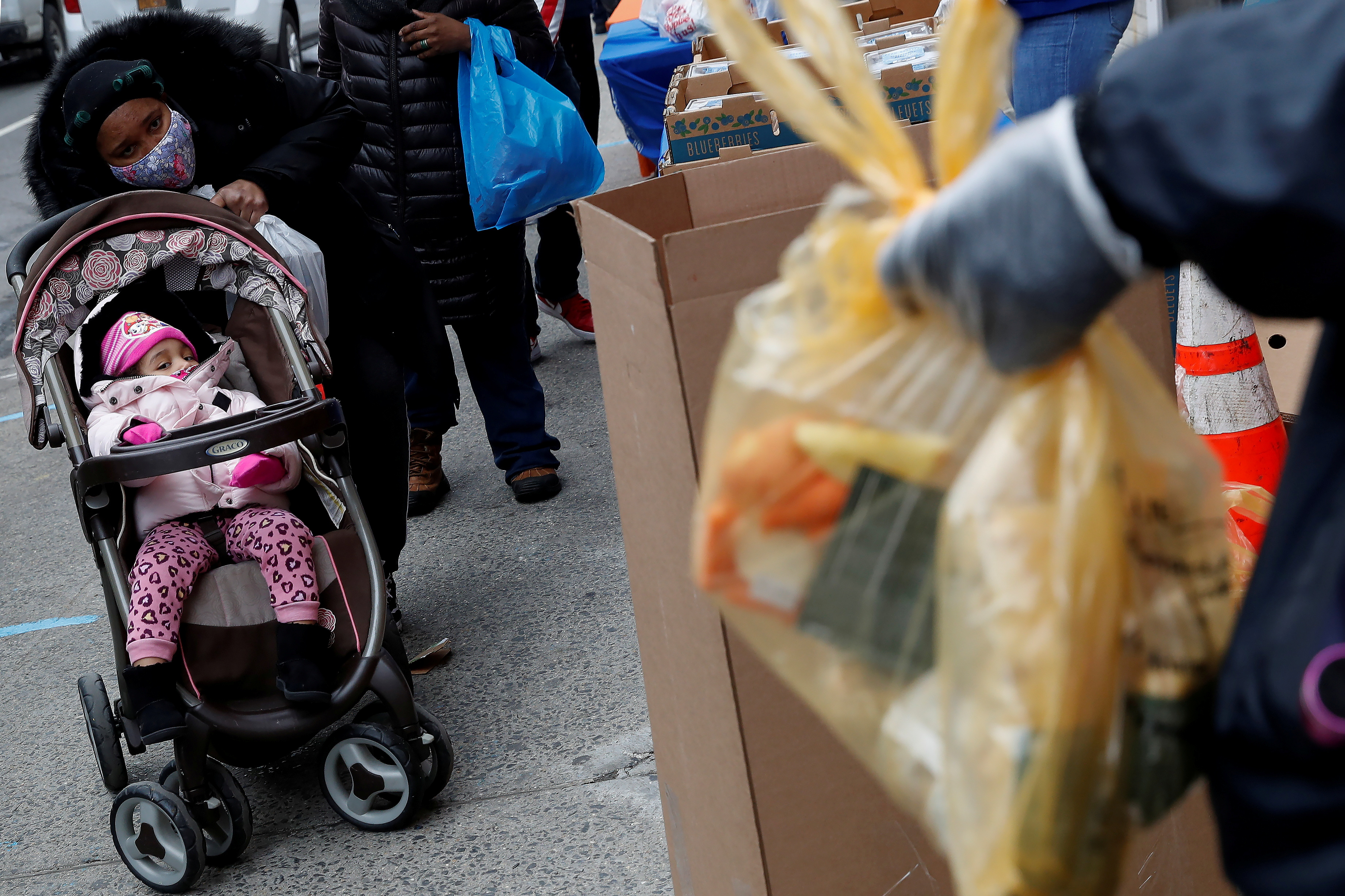 People wait in line for donations outside a food distribution facility amid the spread of the coronavirus disease (COVID-19) in the Harlem section of the Manhattan borough of New York, U.S., January 27, 2021. REUTERS/Shannon Stapleton/File Photo