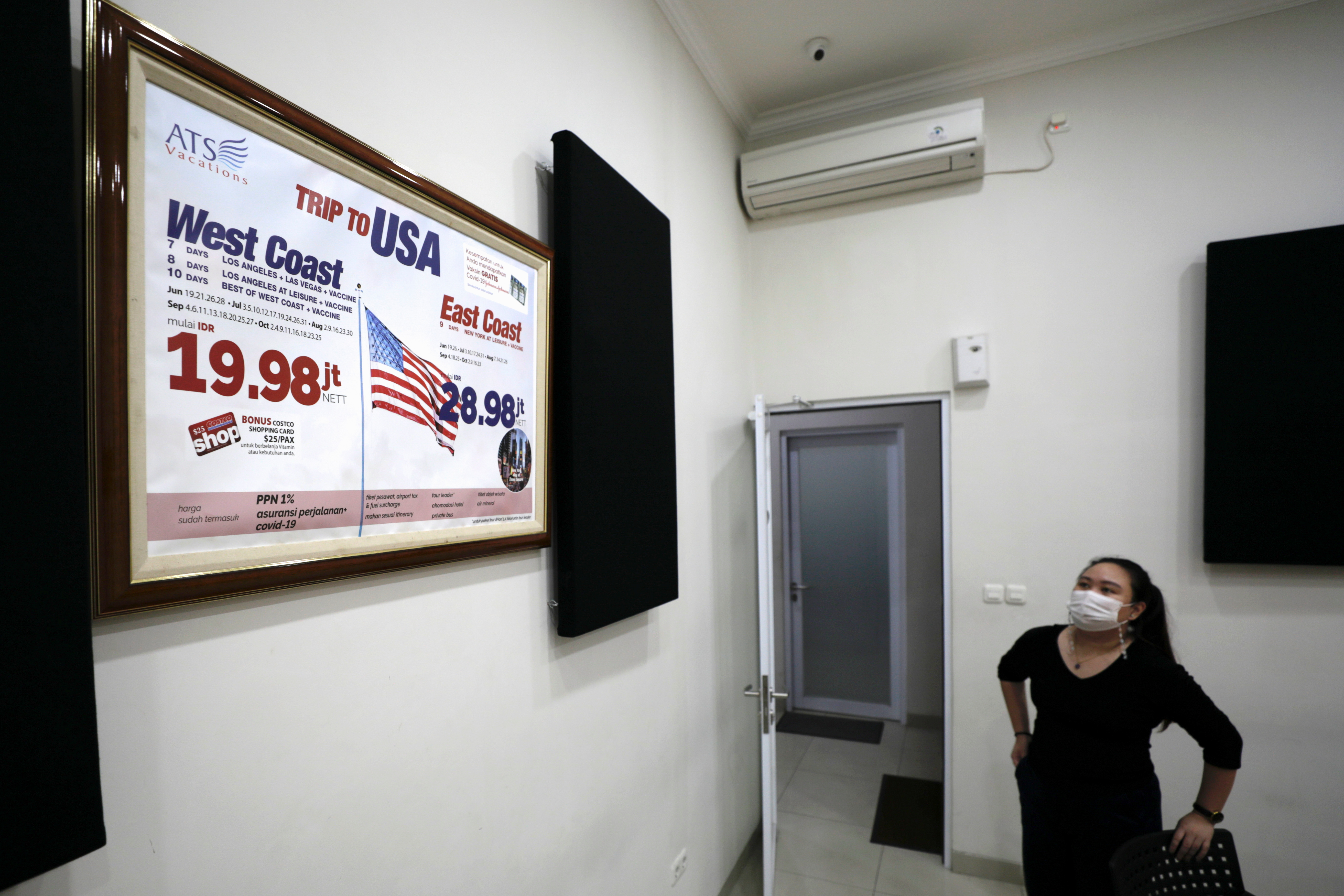 A promotion banner, advertising holiday packages to the U.S. that include a dose of Johnson & Johnson's coronavirus disease (COVID-19) vaccine, is seen inside a meeting room of Anugerah Tour Semesta travel agency in Jakarta, Indonesia, June 14, 2021. Picture taken June 14, 2021. REUTERS/Willy Kurniawan