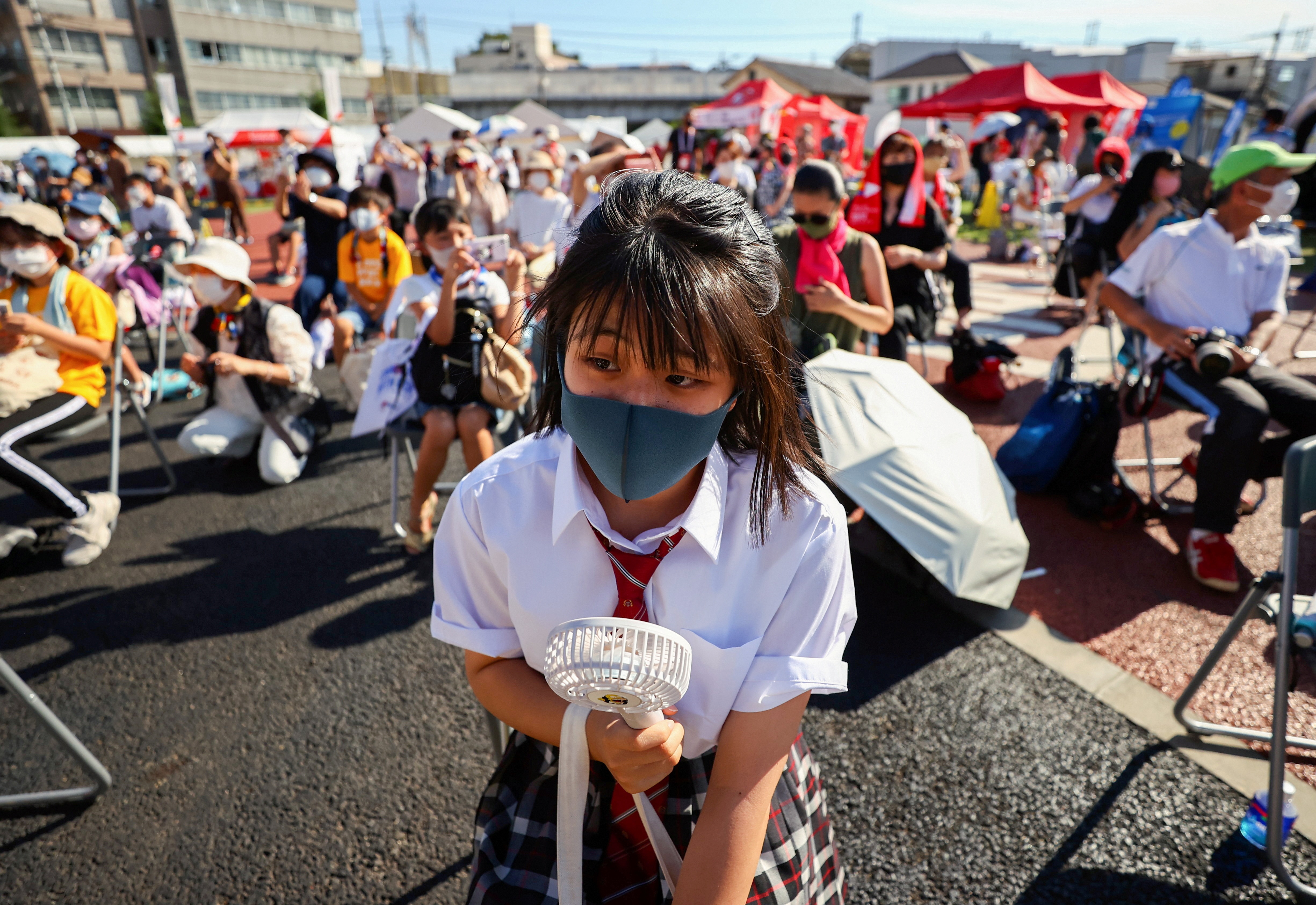 A family member of a torch relay runner wearing a protective mask uses a portable electric fan to cool down as she attends a torch kiss event during Tokyo 2020 Olympic torch relay celebration at Shinagawa Central Park in Tokyo, Japan, July 21, 2021. REUTERS/Issei Kato