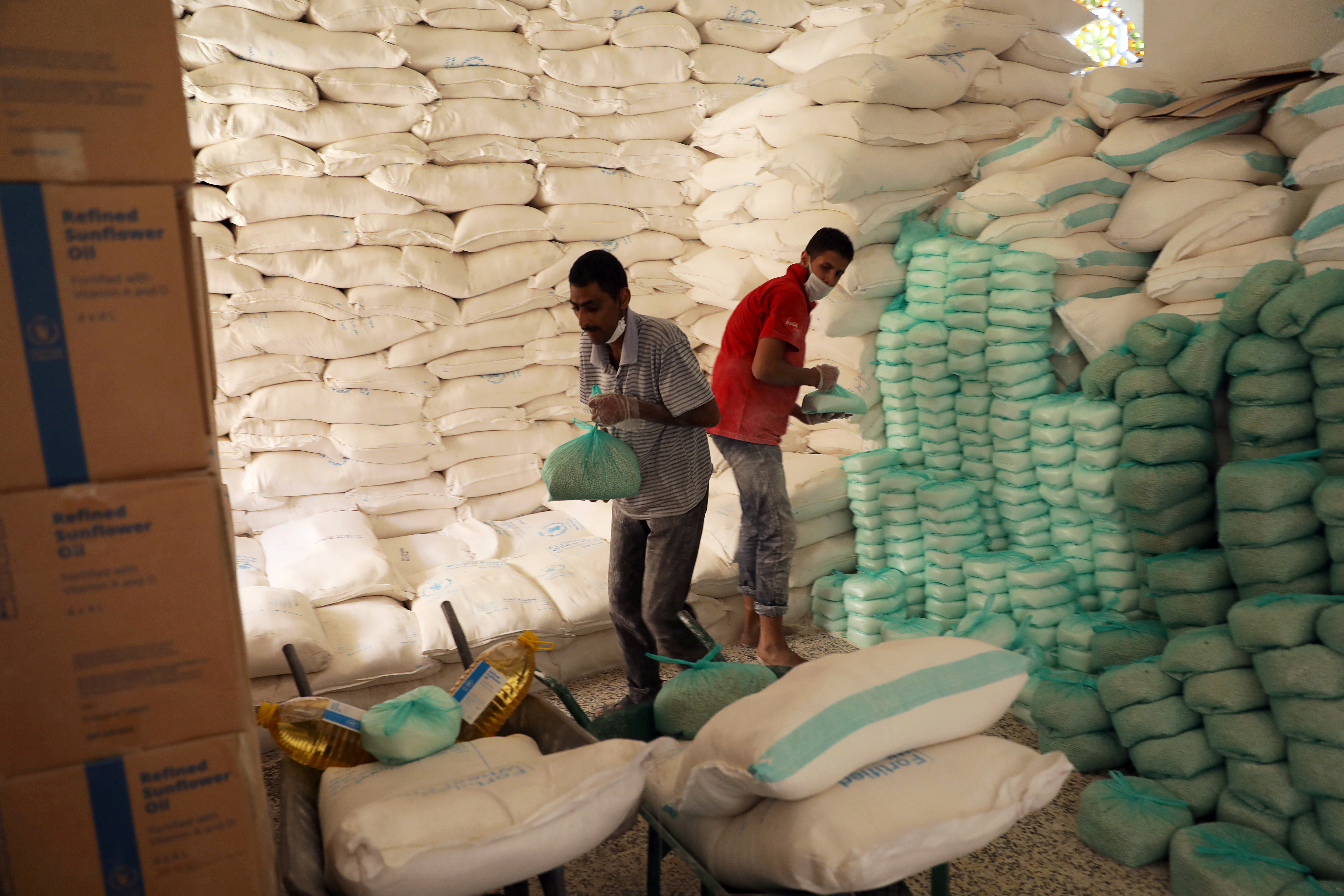 Workers prepare foodstuff for beneficiaries at a food distribution center supported by the World Food Program in Sanaa, Yemen June 3, 2020. REUTERS/Khaled Abdullah/File Photo
