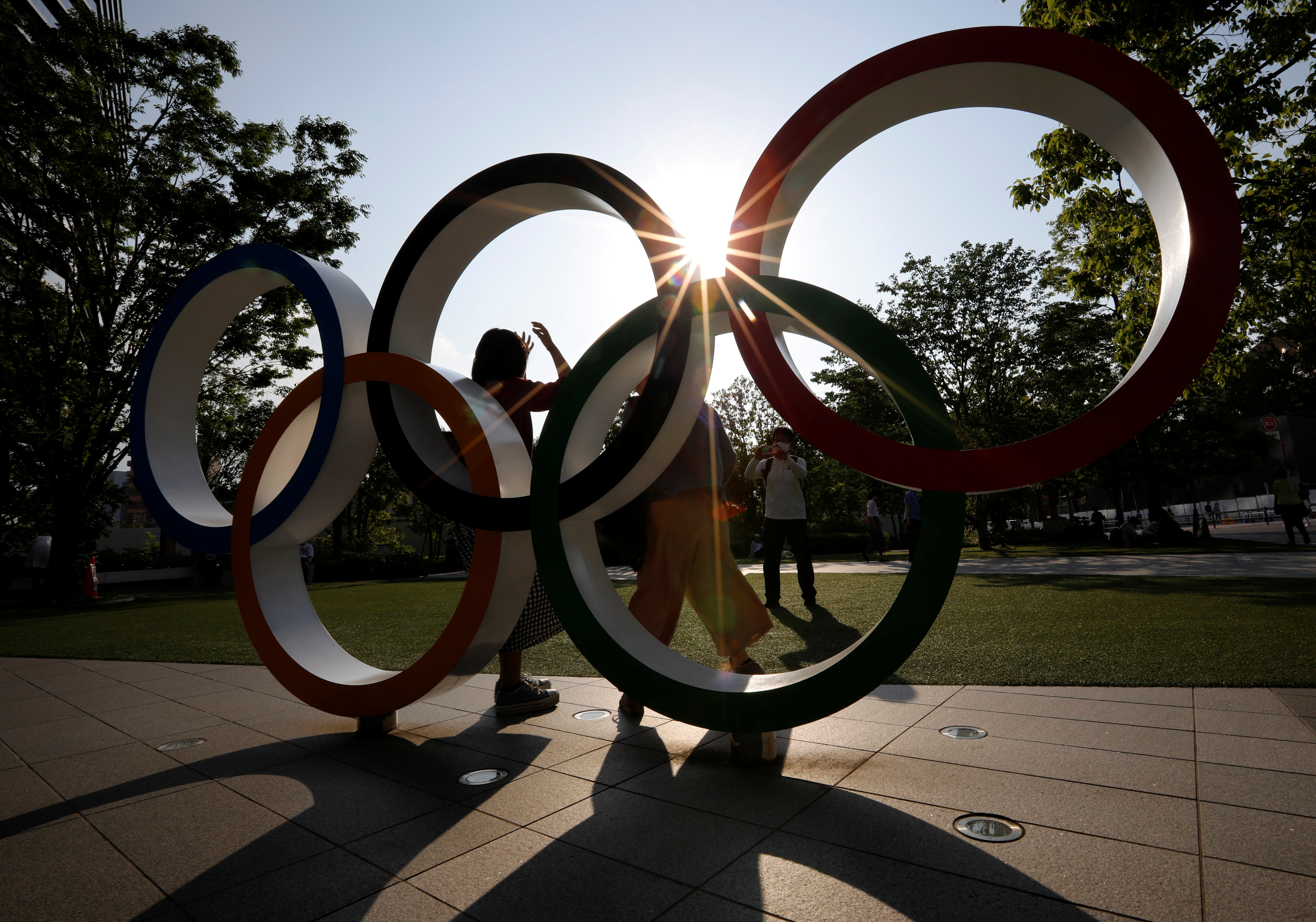 Visitors try to take photos in front of the Olympic Rings monument outside the Japan Olympic Committee (JOC) headquarters near the National Stadium, the main stadium for the 2020 Tokyo Olympic Games that have been postponed to 2021 due to the coronavirus disease (COVID-19) outbreak, in Tokyo, Japan May 30, 2021.  REUTERS/Issei Kato
