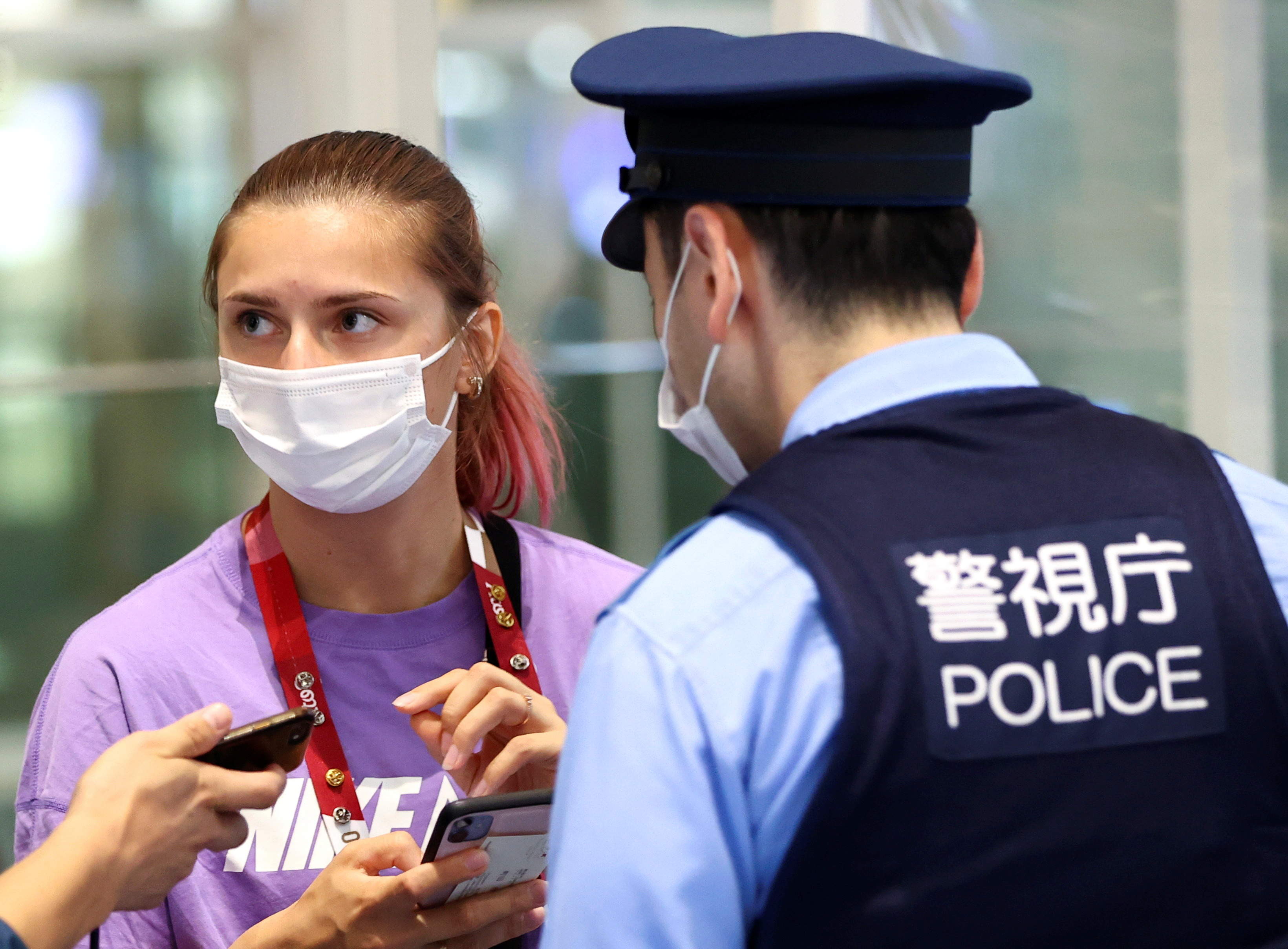 Belarusian sprinter Krystsina Tsimanouskaya talks with police officers at Haneda international airport in Tokyo, Japan August 1, 2021.  REUTERS/Issei Kato/Files