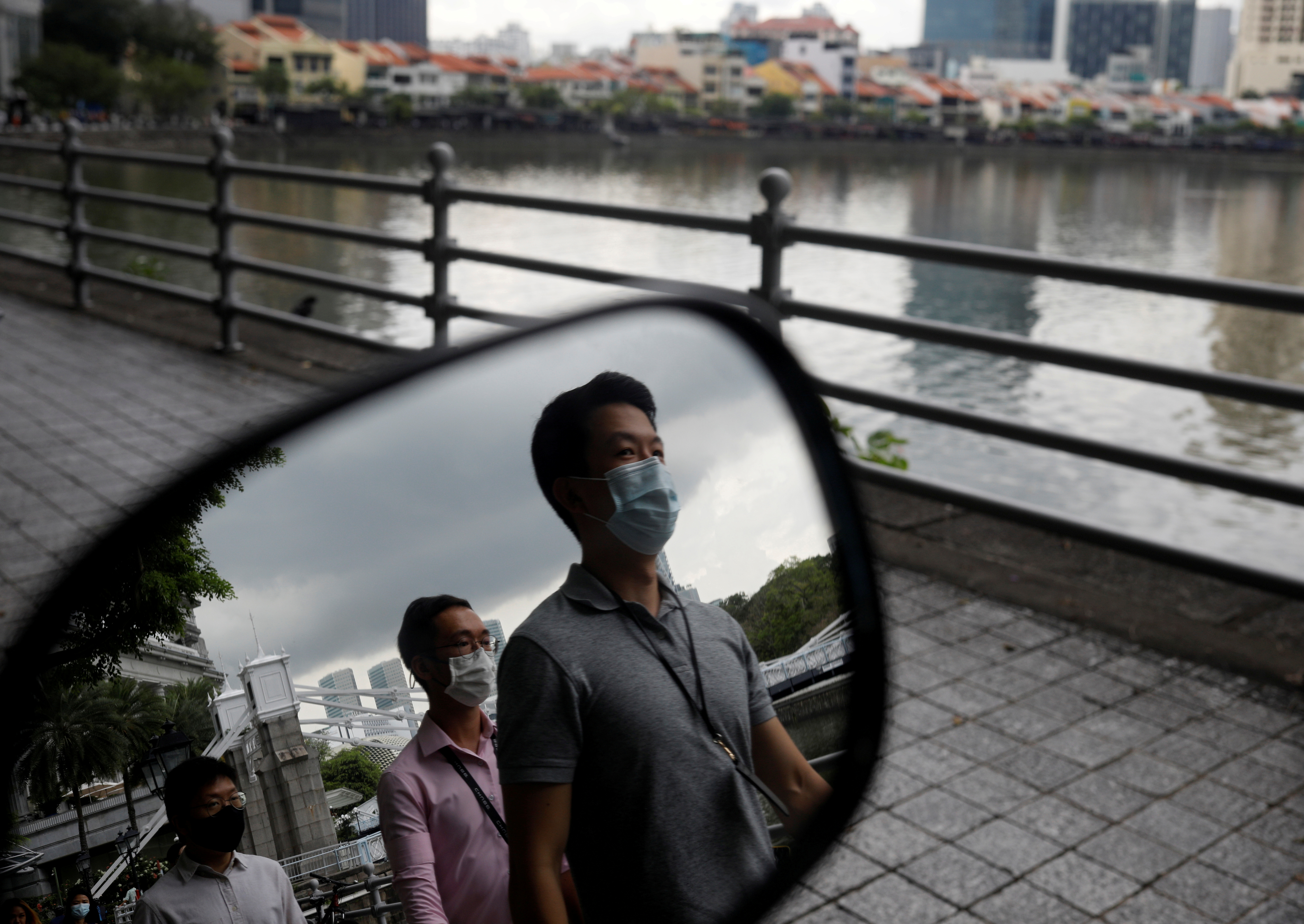 People wearing face masks as a precaution against the coronavirus disease (COVID-19) walk during lunch hour at the central business district in Singapore, December 14, 2020.  REUTERS/Edgar Su/File Photo