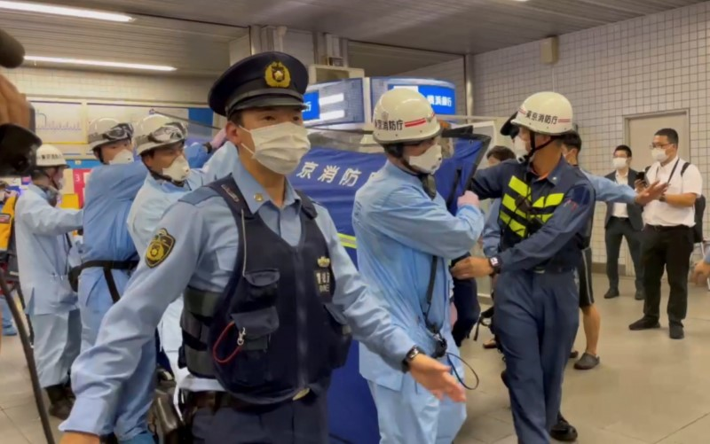 Police escort rescue workers carrying a person through a train station after a knife attack on a train in Tokyo, Japan August 6, 2021 in this still image taken from video obtained by REUTERS