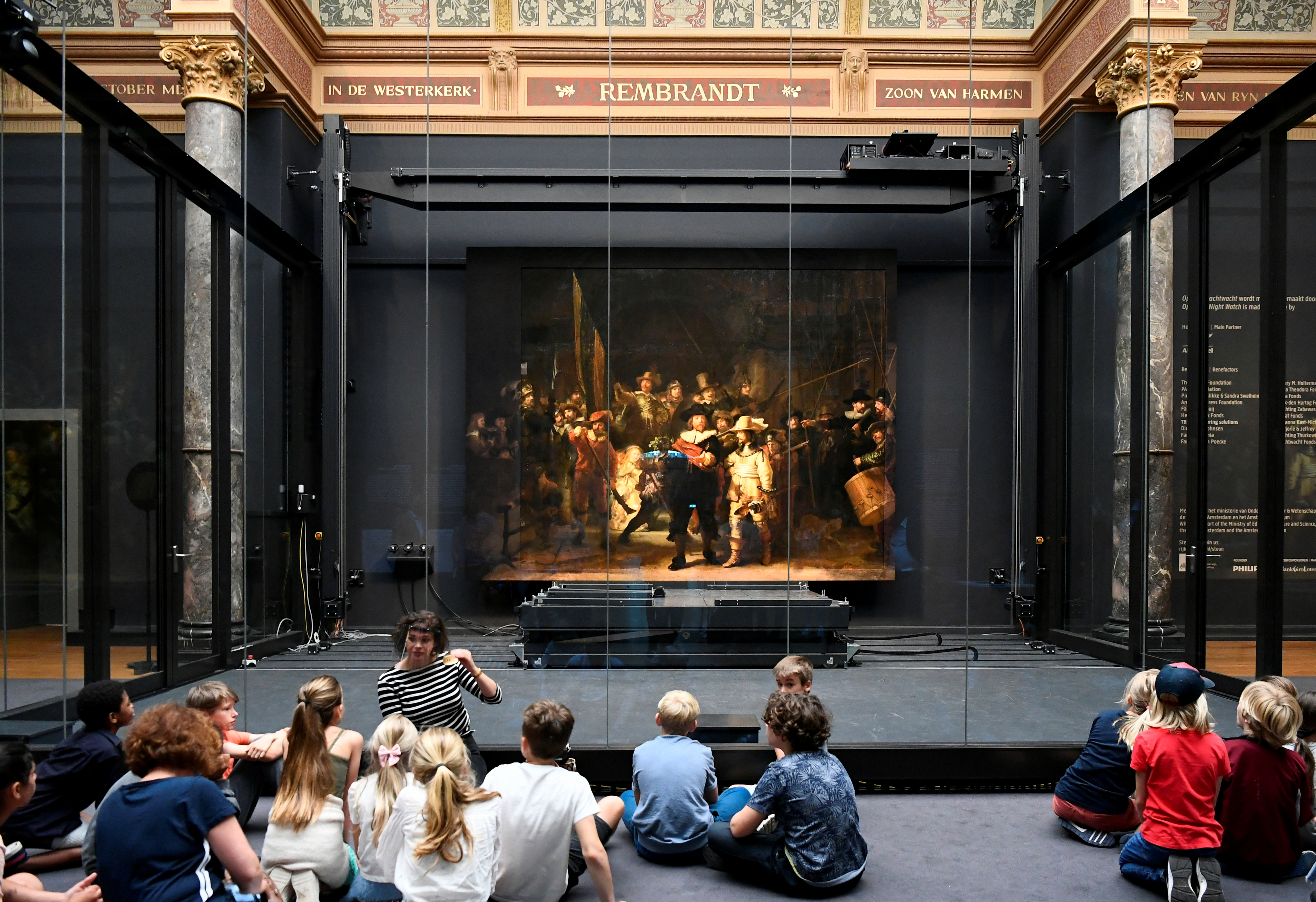 Children look at Rembrandt's famed Night Watch, which is back on display in what researchers say in its original size, with missing parts temporarily restored in an exhibition aided by artificial intelligence, at Rijksmuseum in Amsterdam, Netherlands June 23, 2021. REUTERS/Piroschka van de Wouw