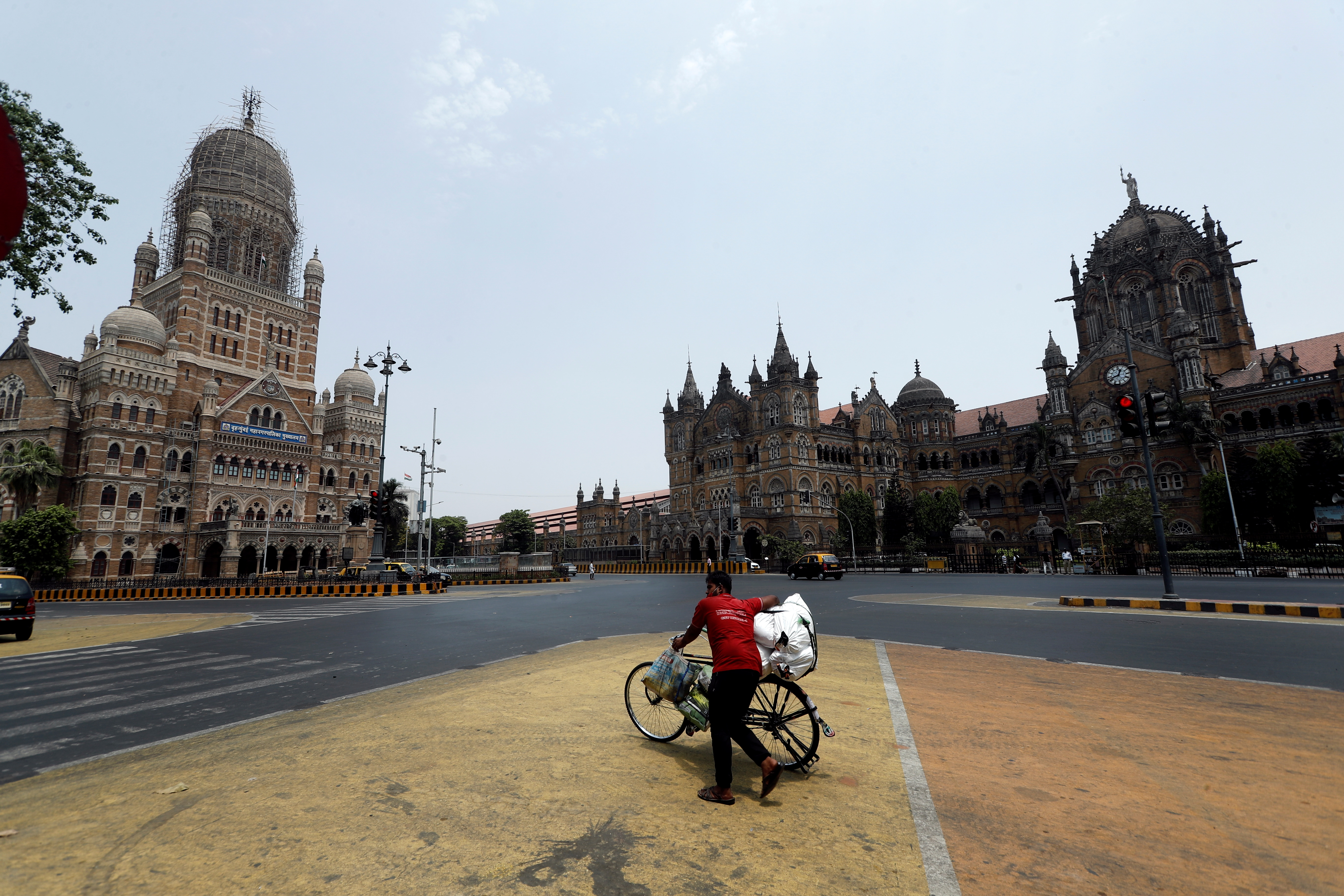A man walks with his bicycle in front of the Brihanmumbai Municipal Corporation (BMC) building and the Chhatrapati Shivaji Maharaj Terminus (CSMT) during a weekend lockdown to limit the spread of the coronavirus disease (COVID-19) in Mumbai, India, April 10, 2021. REUTERS/Francis Mascarenhas