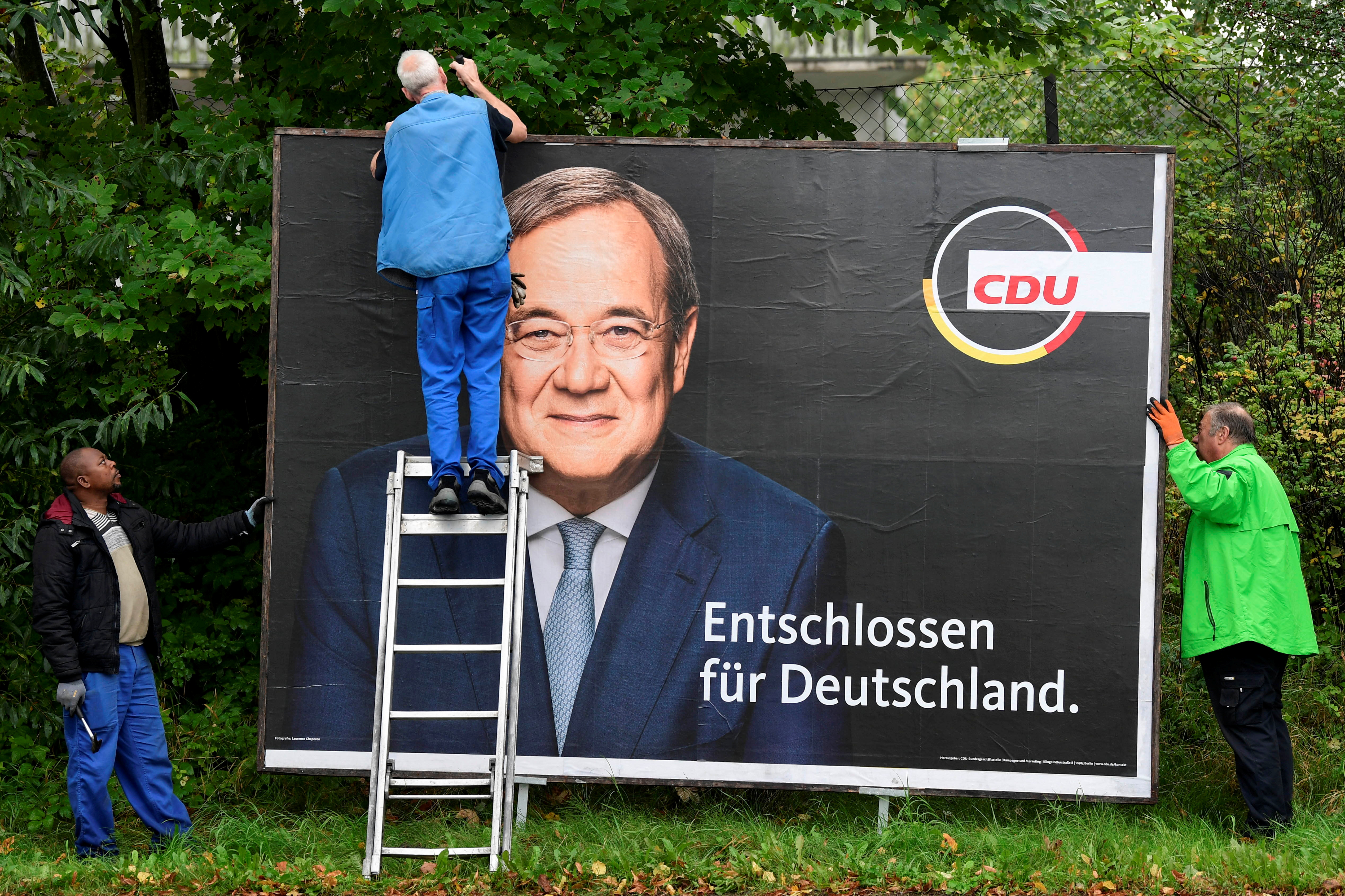 Workers remove an election campaign poster showing Armin Laschet, candidate for Chancellor of Germany's Christian Democratic Union party CDU, the day after the German general elections, in Bad Segeberg near Hamburg, Germany, September 27, 2021. REUTERS/Fabian Bimmer