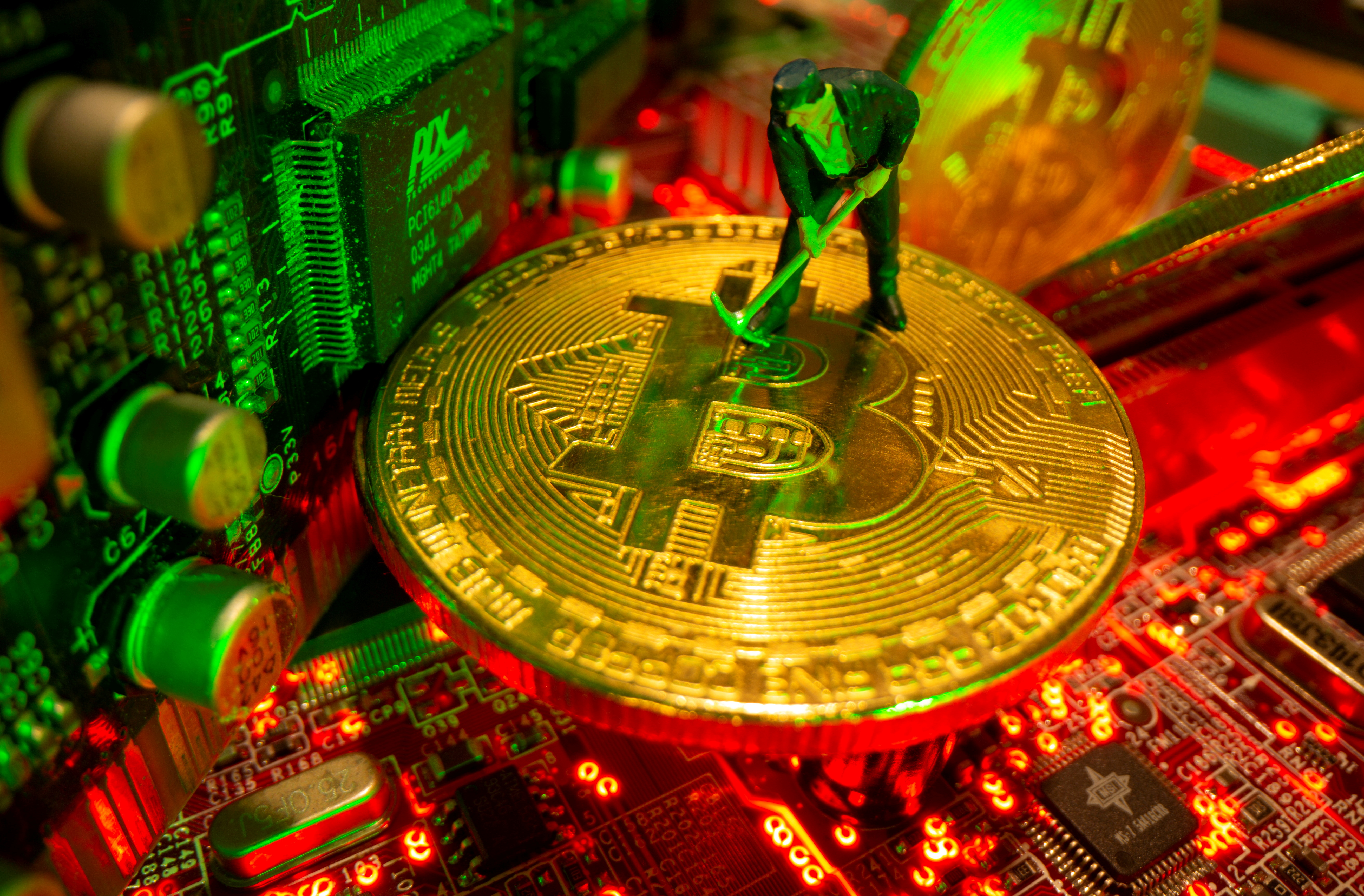 A small toy figure and representations of the virtual currency Bitcoin stand on a motherboard in this picture illustration taken May 20, 2021. REUTERS/Dado Ruvic/Illustration