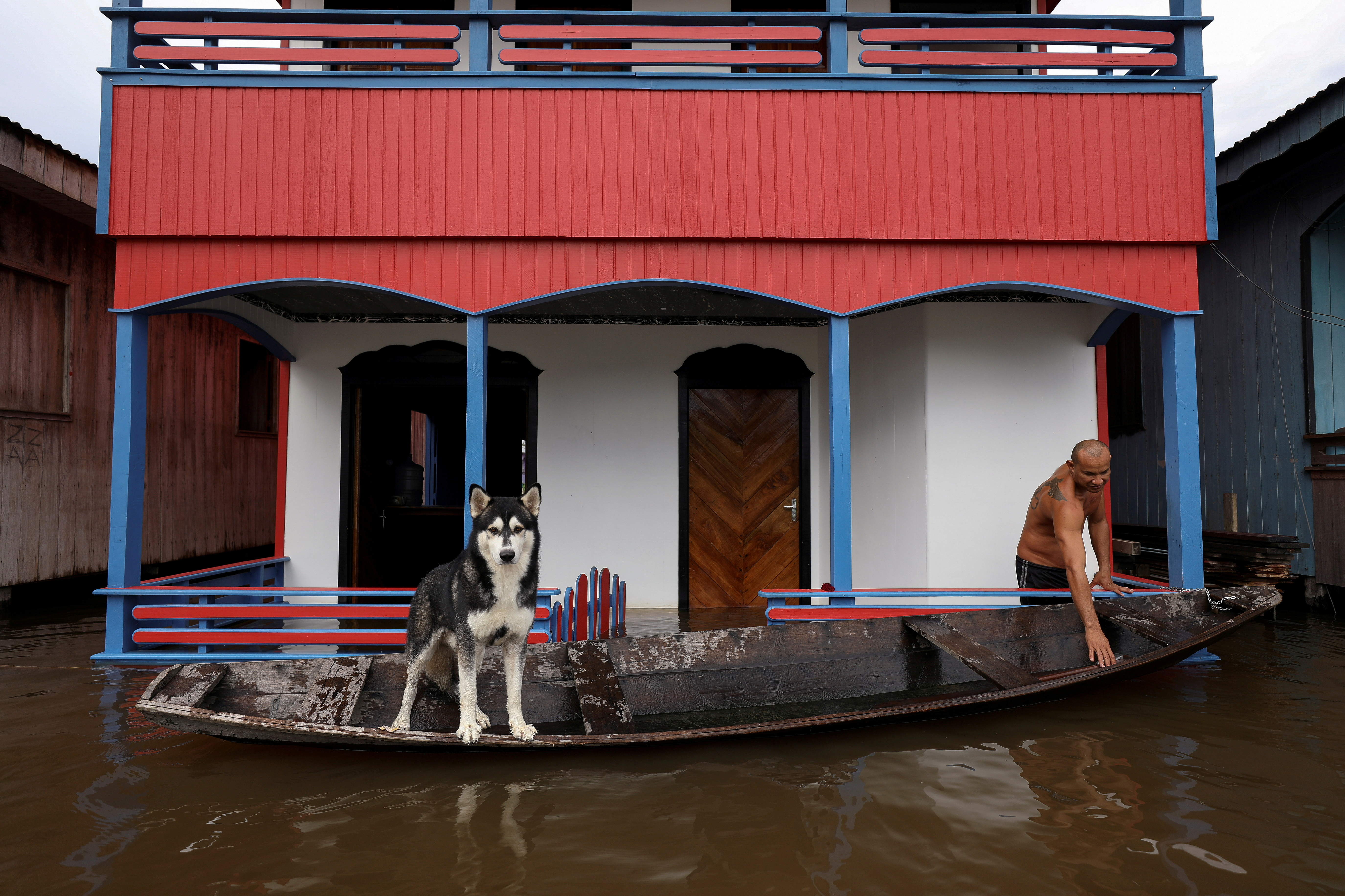 A man prepares his canoe next to his dog on a street flooded by the rising Solimoes river, one of the two main branches of the Amazon River, in Anama, Amazonas state, Brazil May 13, 2021. Picture taken May 13, 2021. REUTERS/Bruno Kelly     TPX IMAGES OF THE DAY