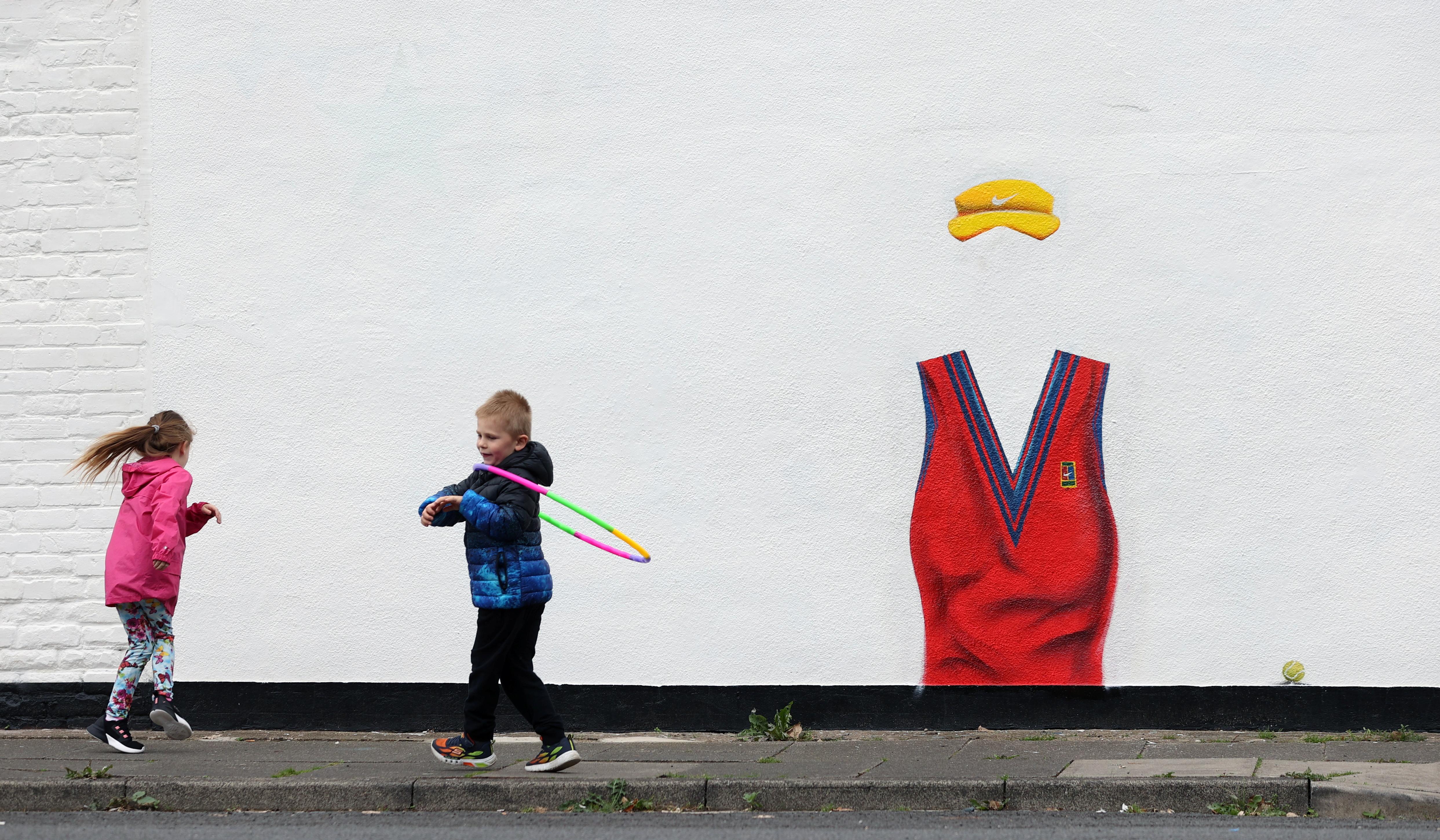 Children play next to a mural dedicated to British tennis player Emma Raducanu in Darlington, Britain September 19, 2021. REUTERS/Lee Smith