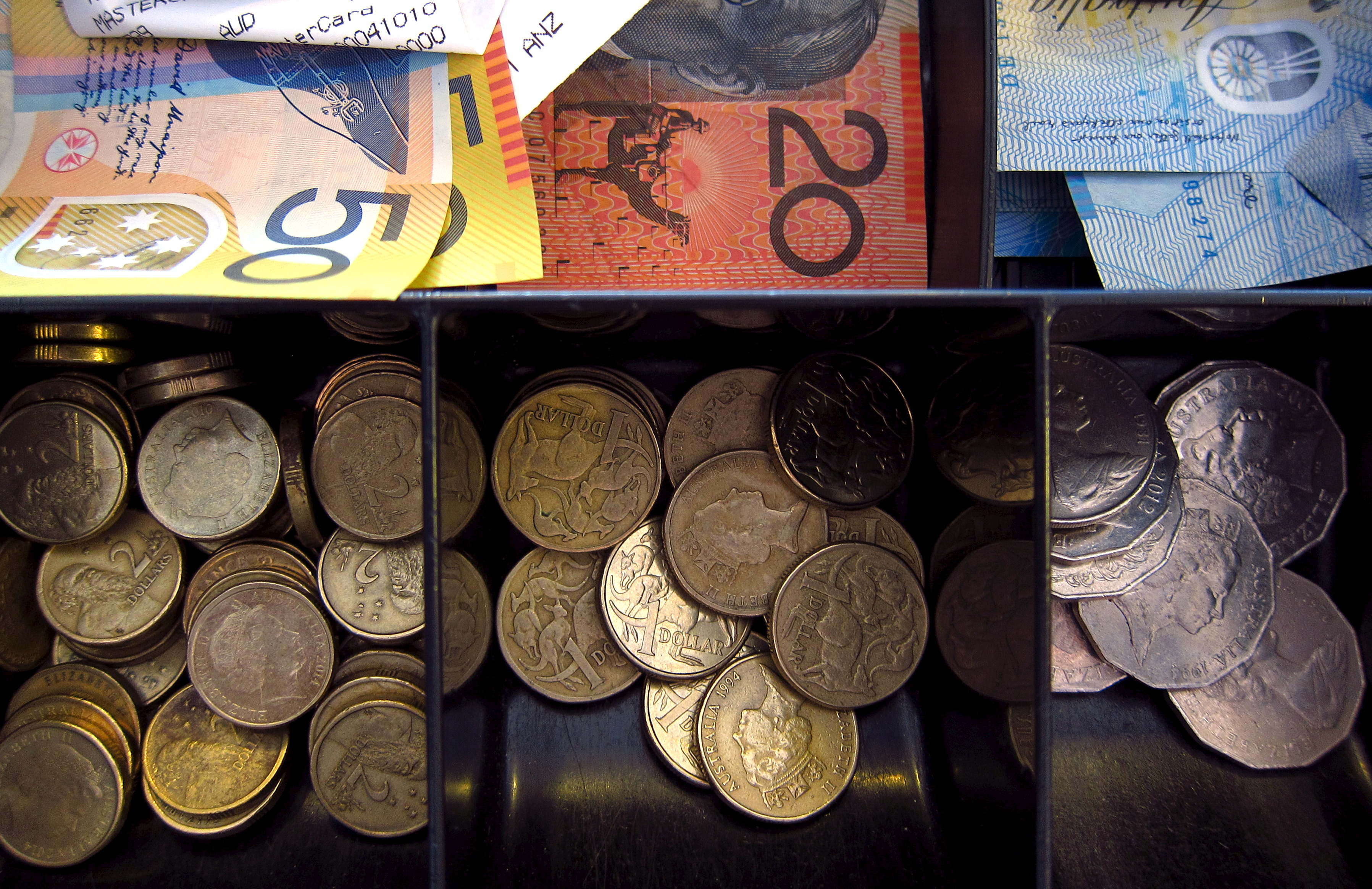 Australian dollar notes and coins can be seen in a cash register at a store in Sydney, Australia, February 11, 2016. The Australian and New Zealand dollars rose to their highest in nearly a week on Thursday as the greenback stayed on the defensive after the head of the Federal Reserve gave investors no reason to expect U.S. rates will be lifted any time soon. REUTERS/David Gray - GF10000304063